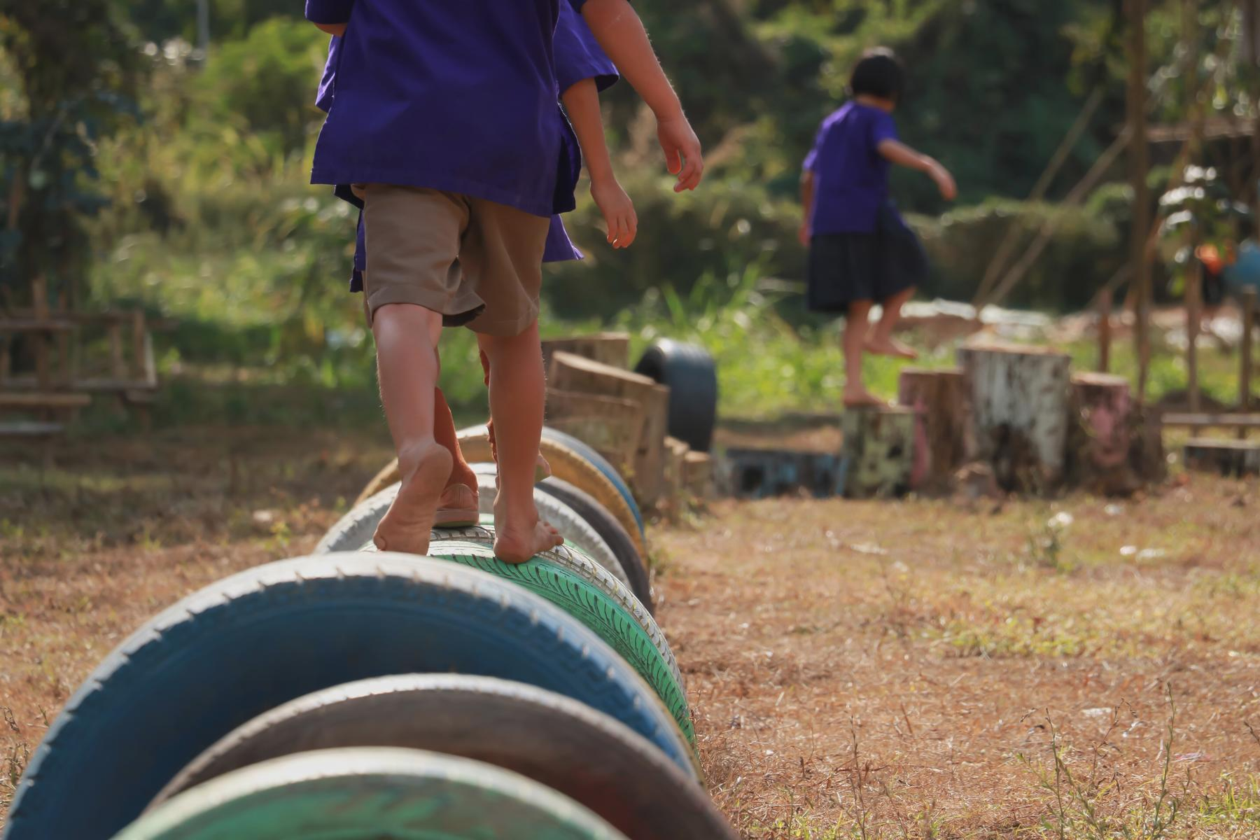 Kids Playing In Playground Running On Tires
