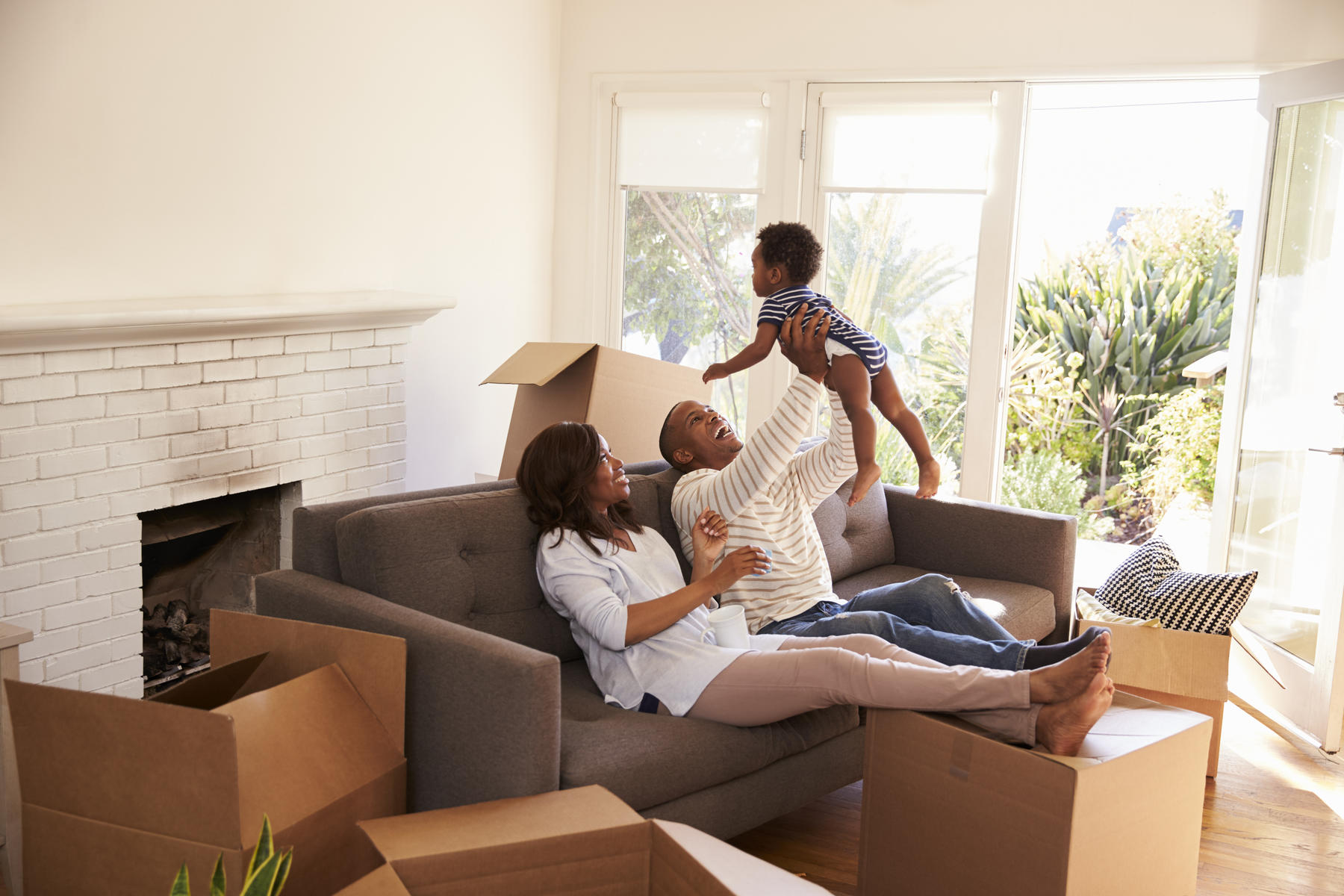 Family Moving Lays On Couch Surrounded With Boxes