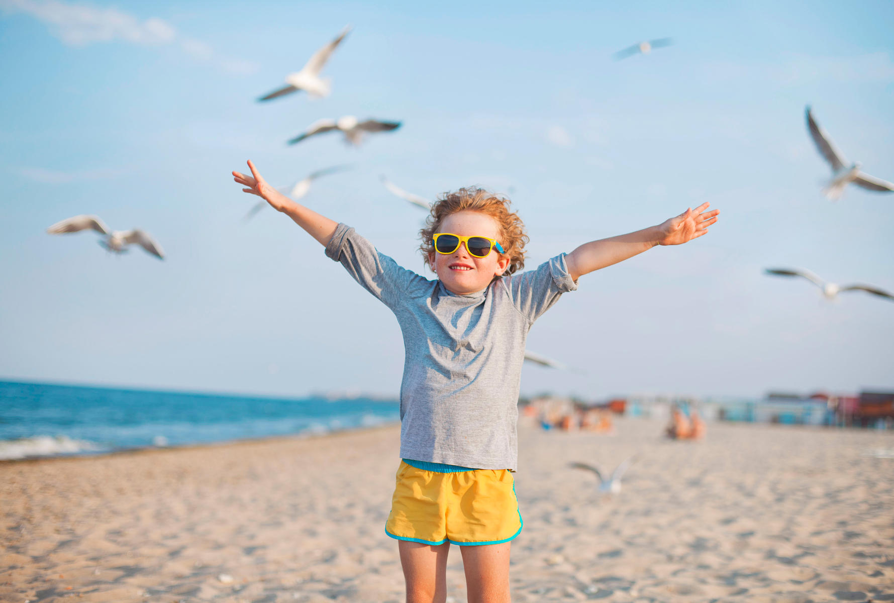 Boy on Beach In Sunglasses Arms Up Around Seagulls