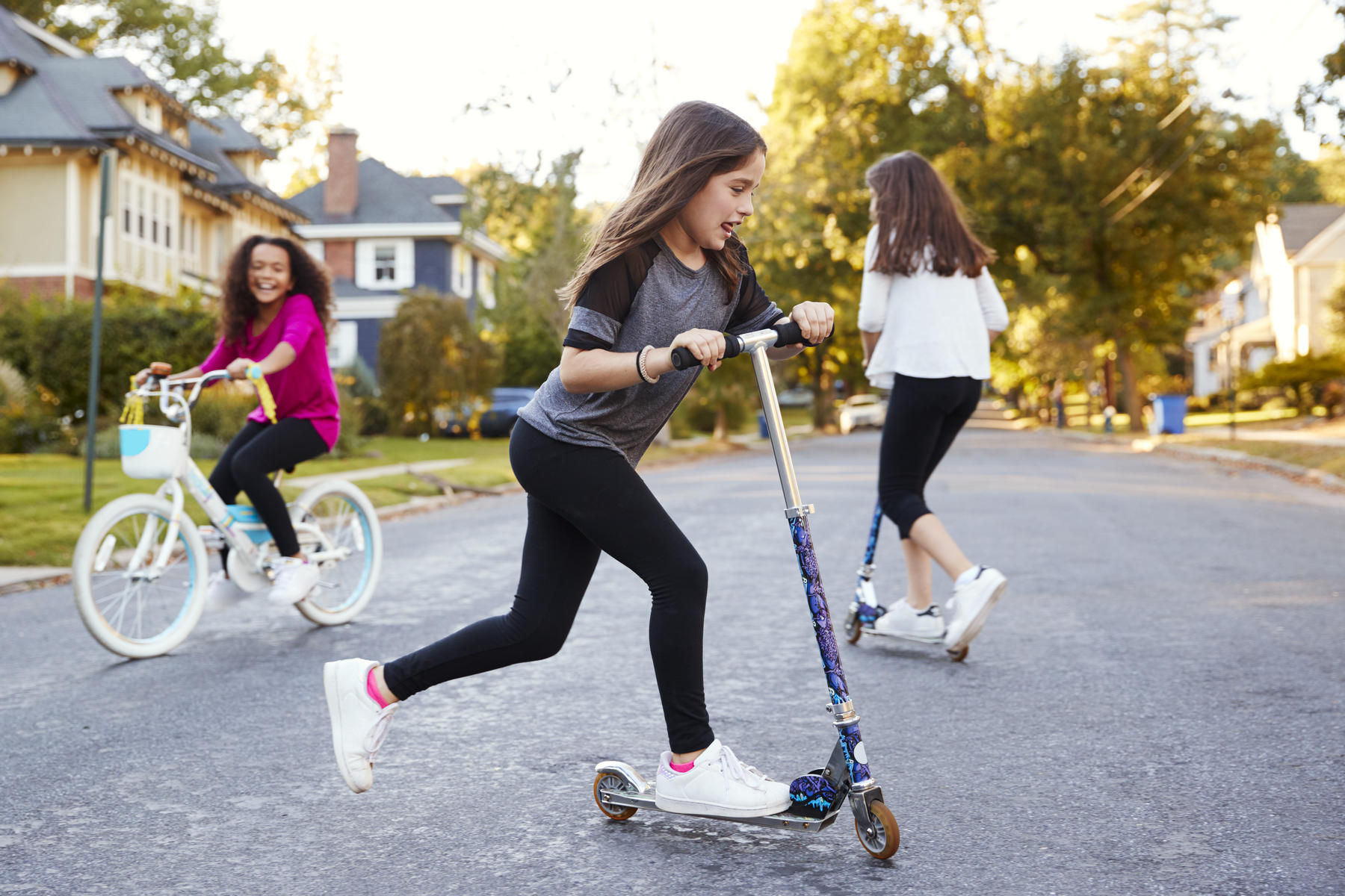 Girls Playing in Street Riding Scooters and Bike