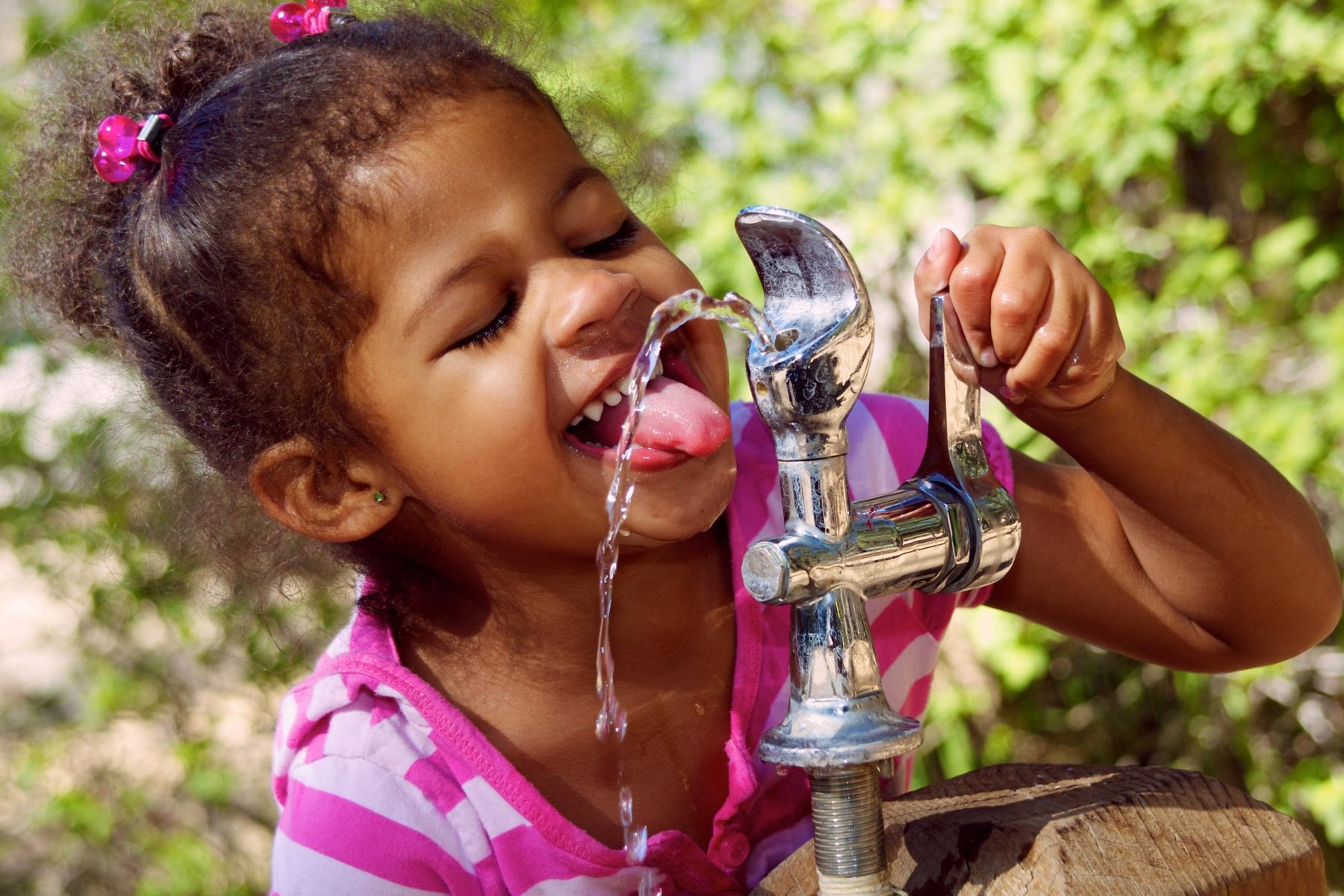 Little Girl Drinking Water From Water Fountain