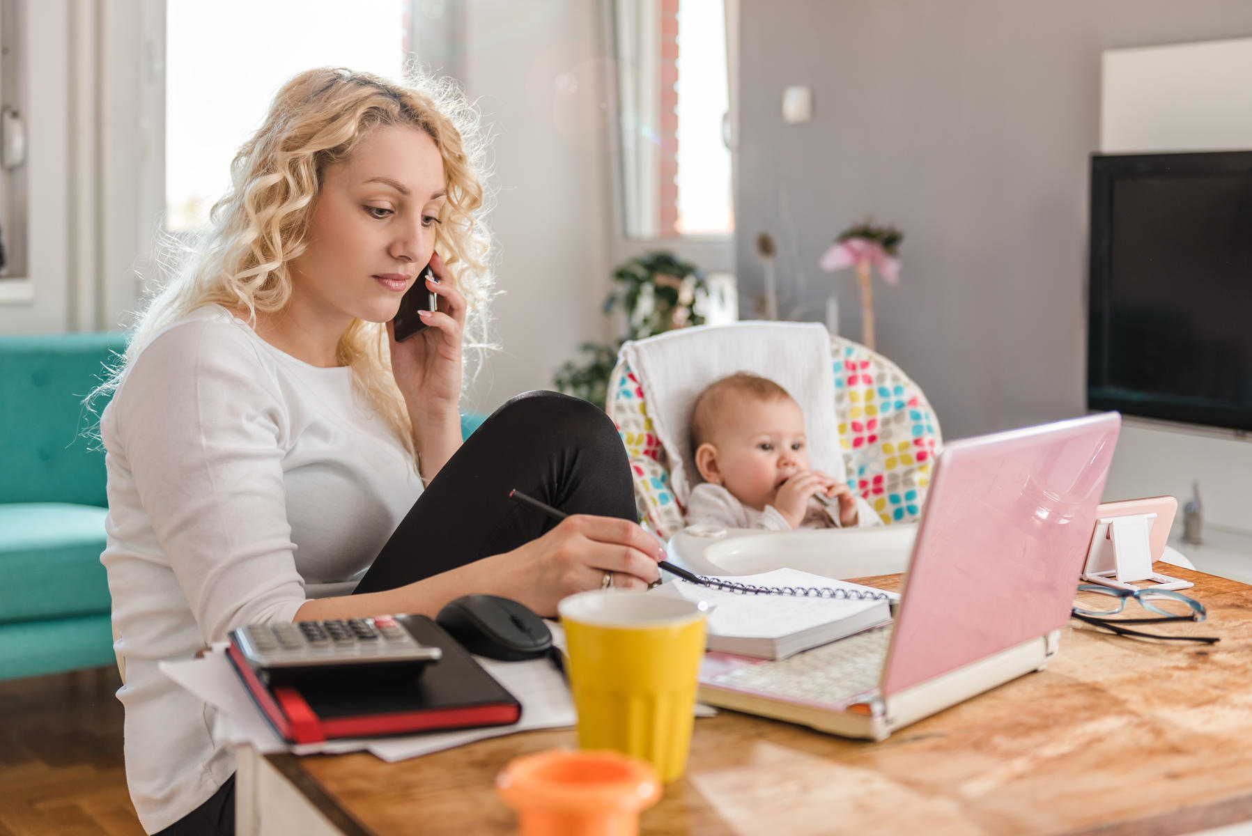 Mother Working From Home With Baby in High Chair