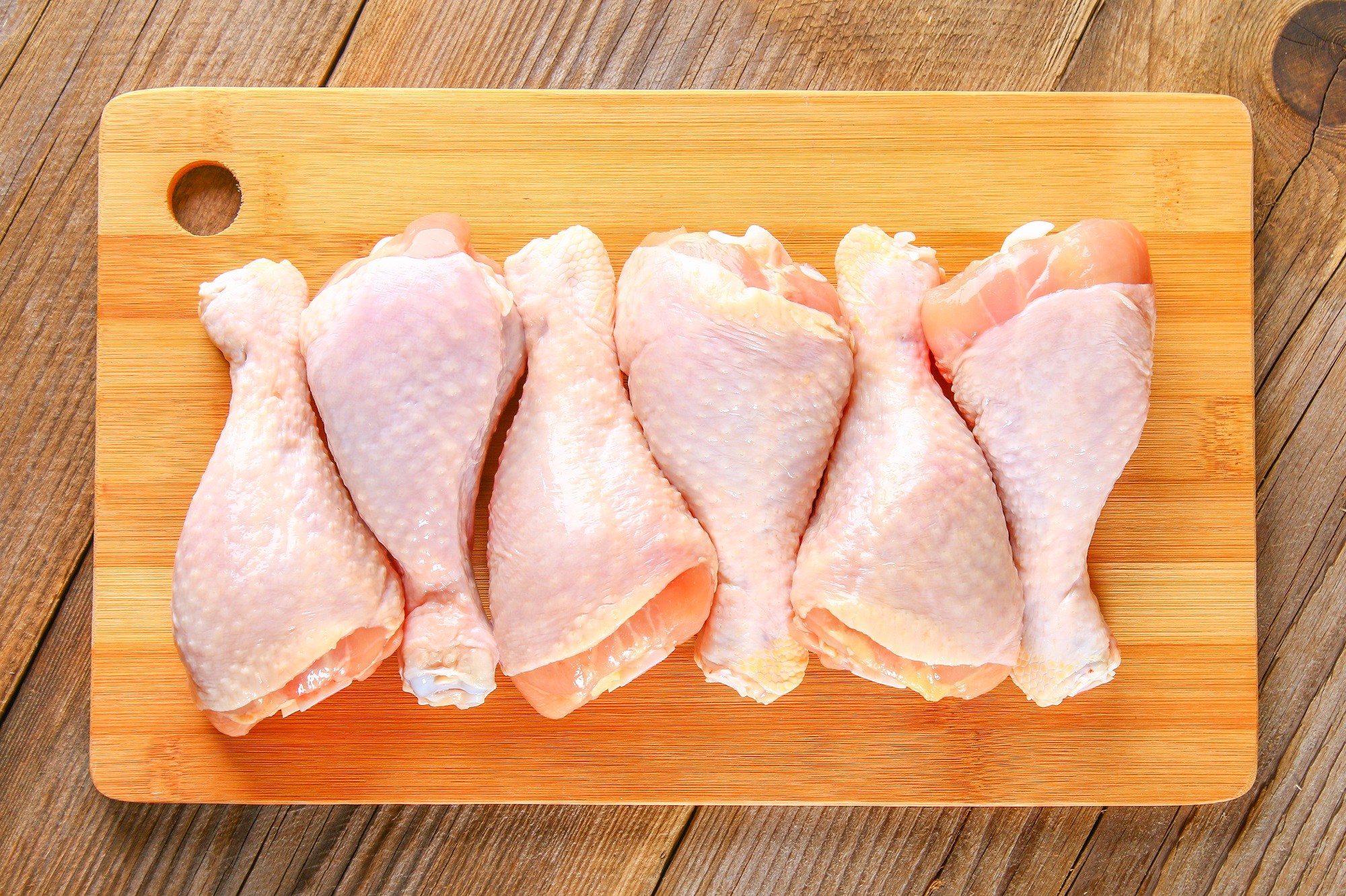 Raw Chicken Legs on Wooden Cutting Board