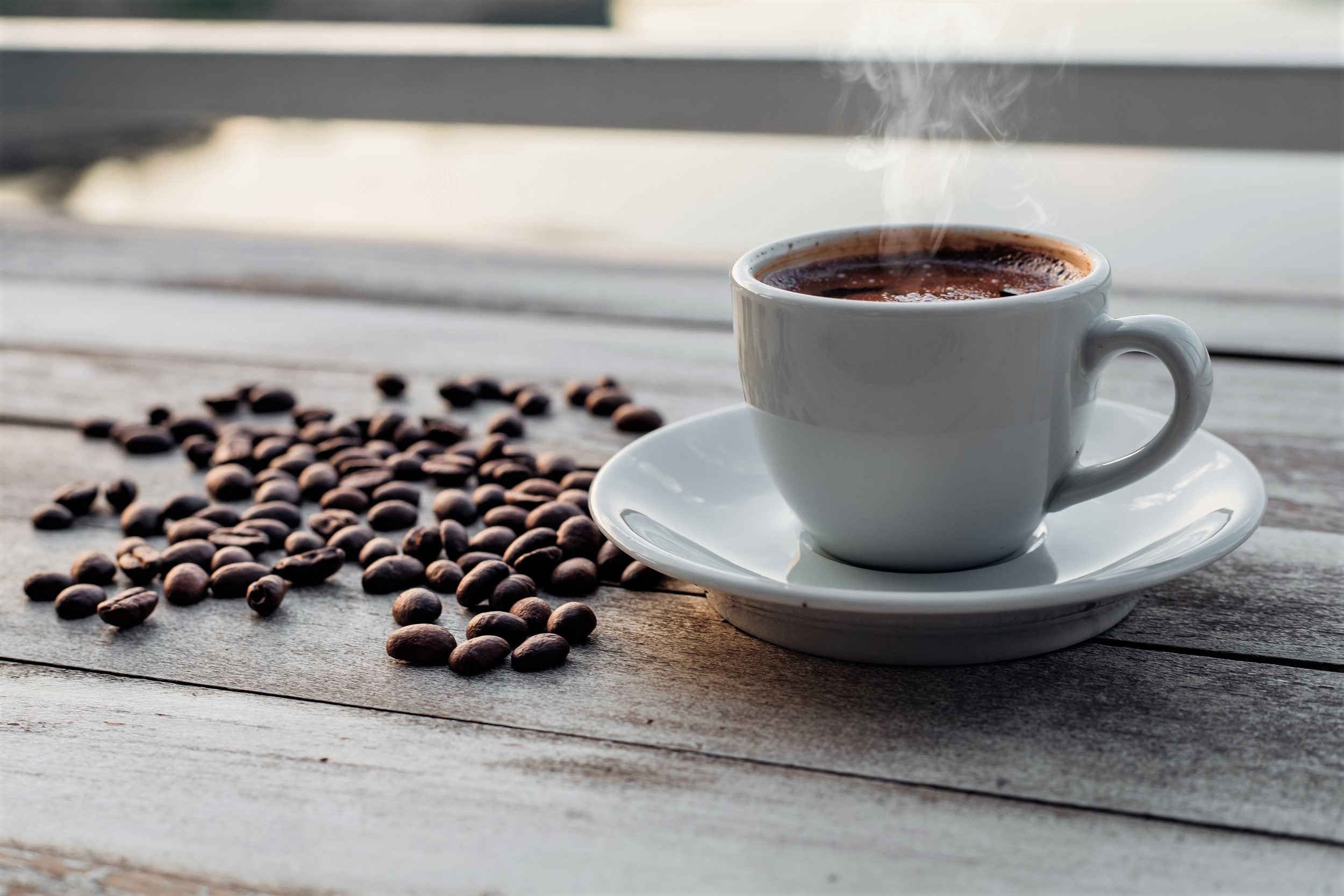 Steaming Hot Cup of Coffee on Wooden Table with Coffee Beans