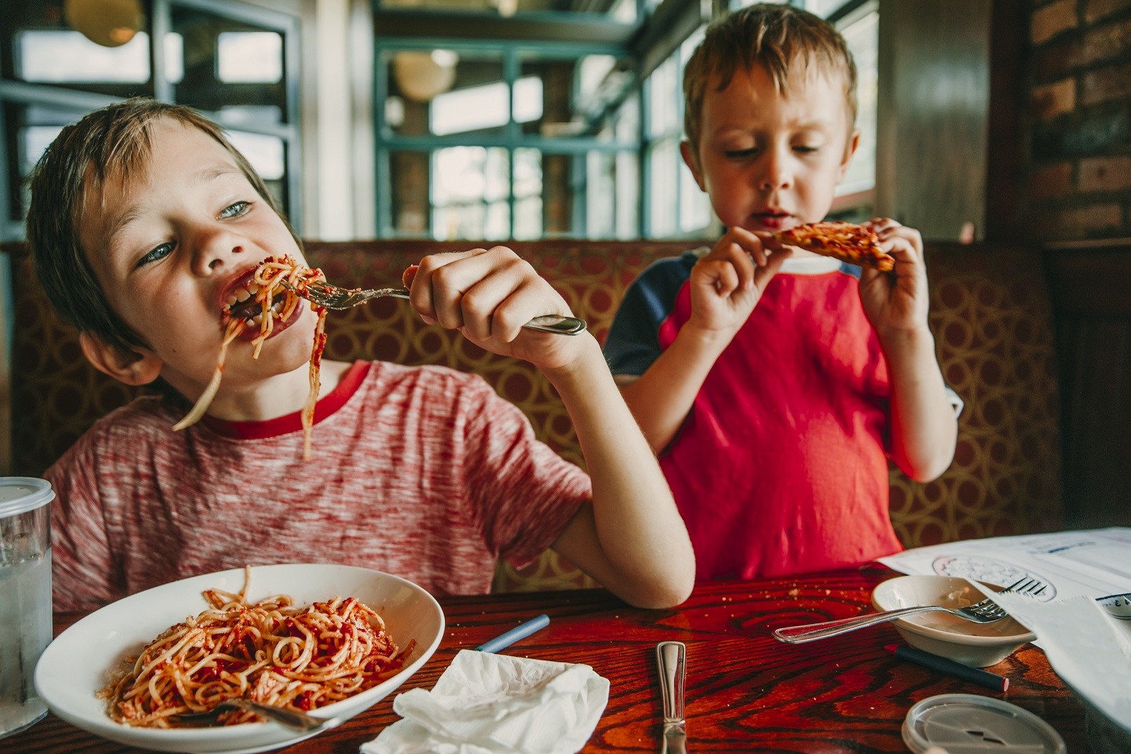 Two Boys Eating Messy In Restaurant Pasta and Pizza