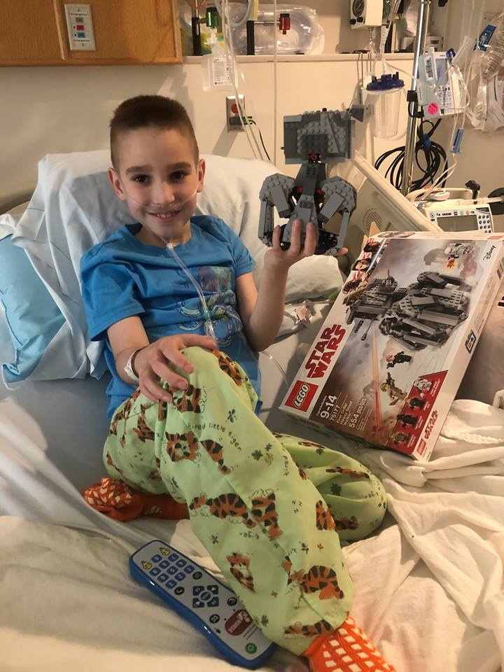 Noah McFall Holding Star Wars Legos in Hospital Bed