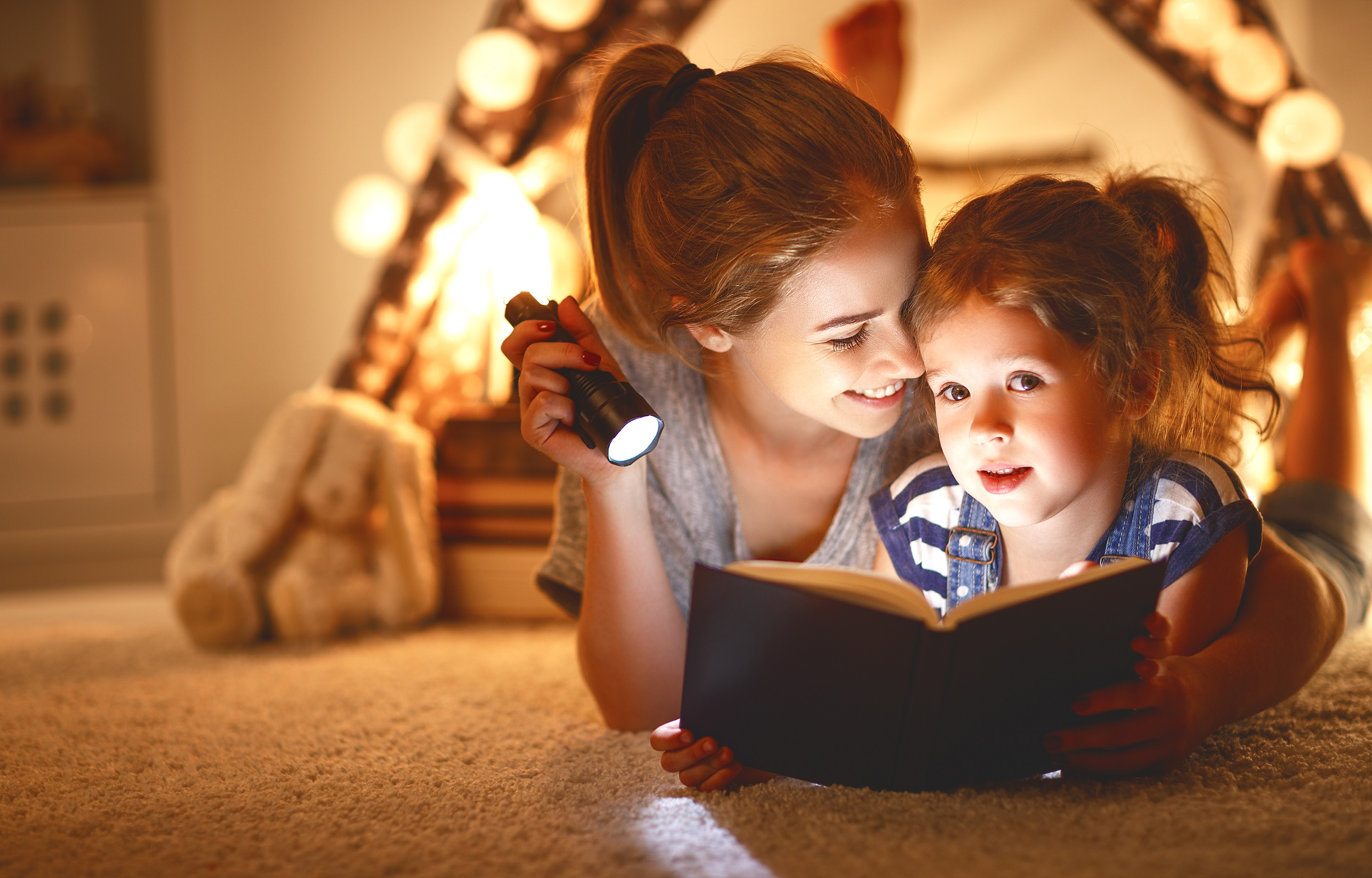 Mother Reading Book With Daughter Inside Tent Twinkle Lights