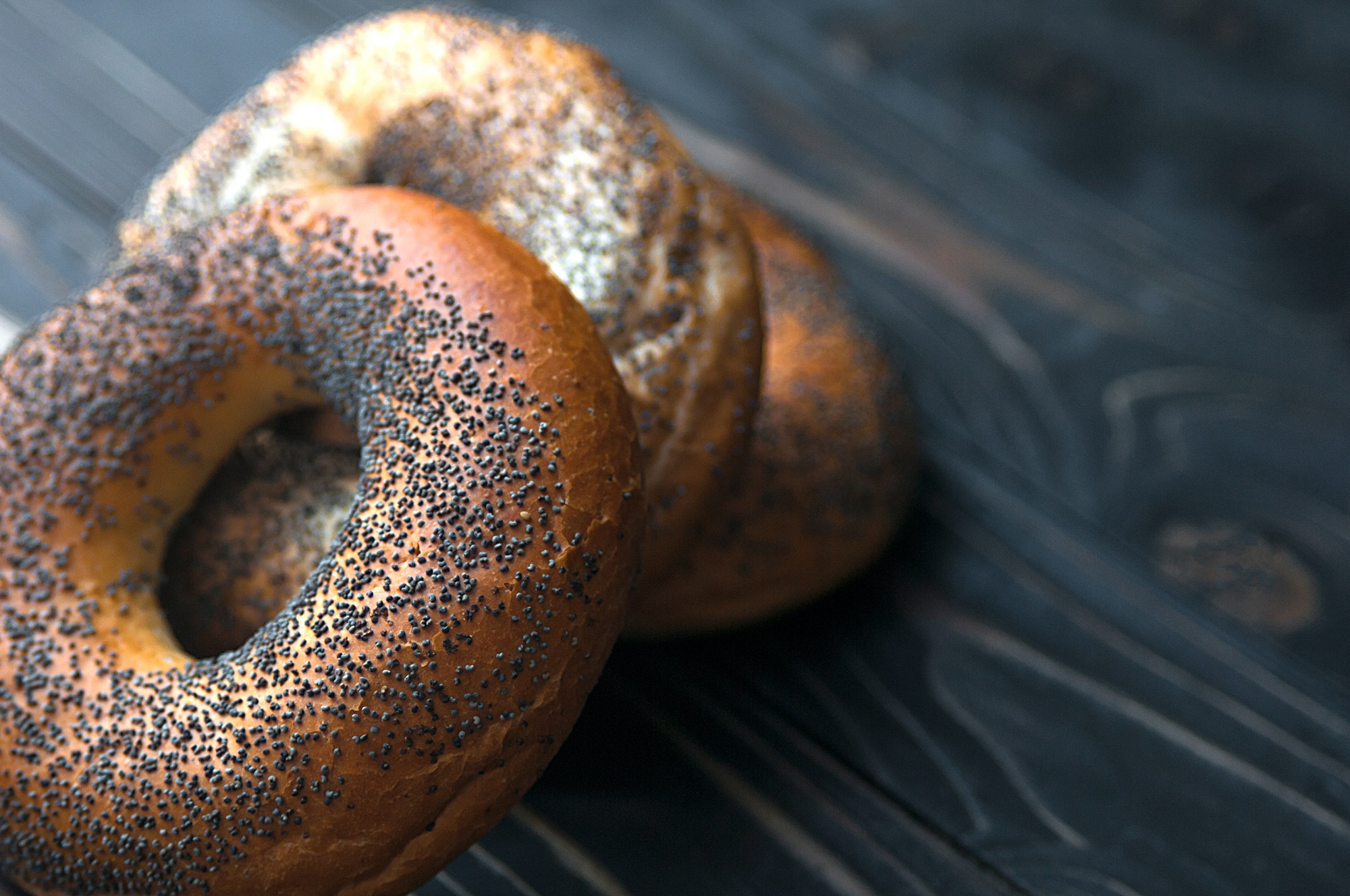 Poppy Seed Bagels on Black Wooden Tabletop