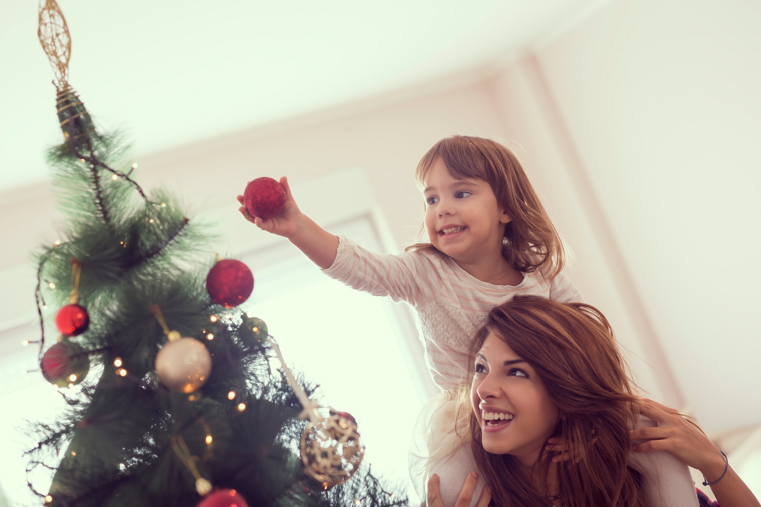 Happy Mother and Daughter Decorating Christmas Tree