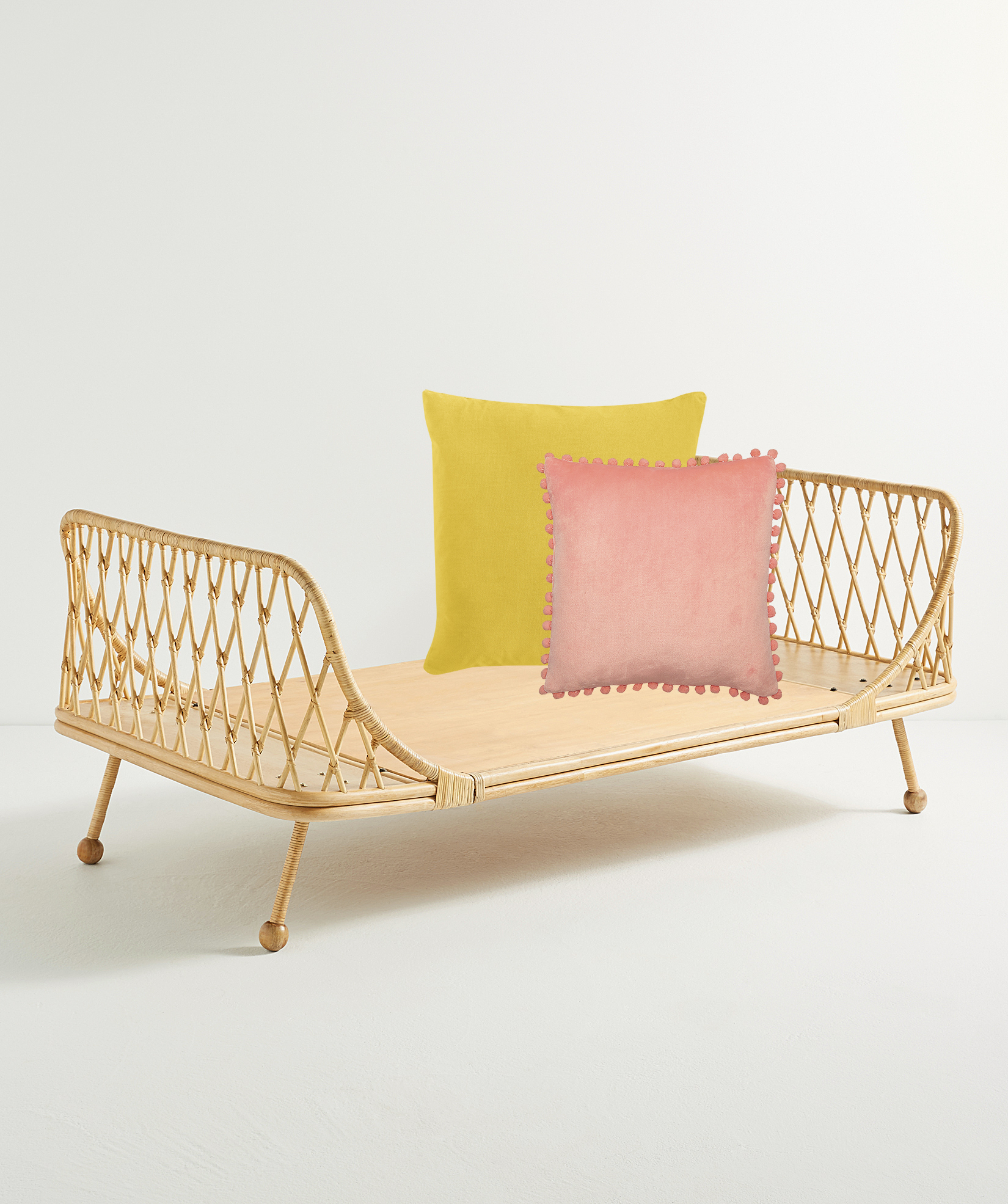 Antique Pan Rattan Daybed with Yellow Velvet Throw Pillow and Pink Pom Pom Throw Pillow
