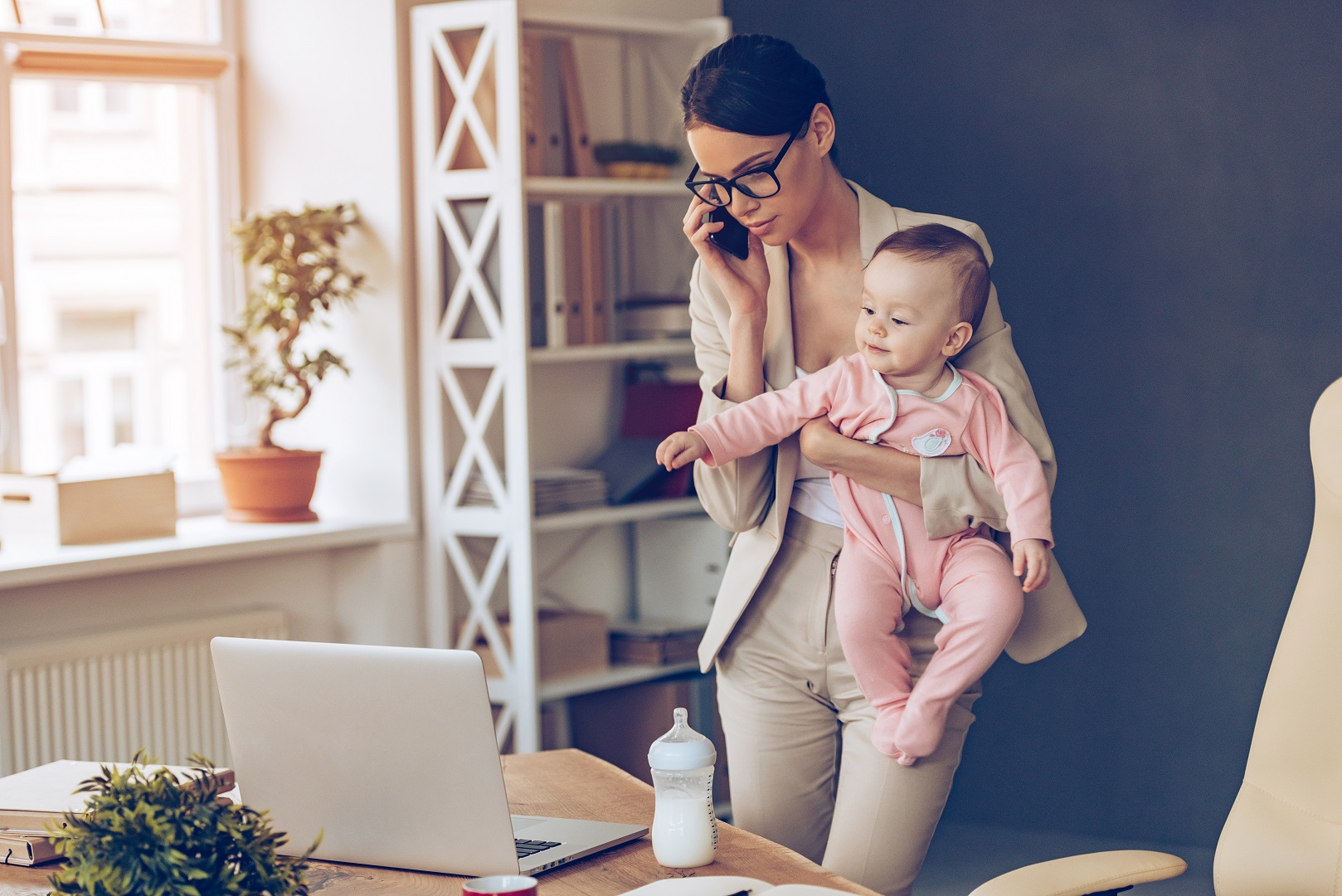 Mom Holding Baby Standing Working From Home On Phone Call