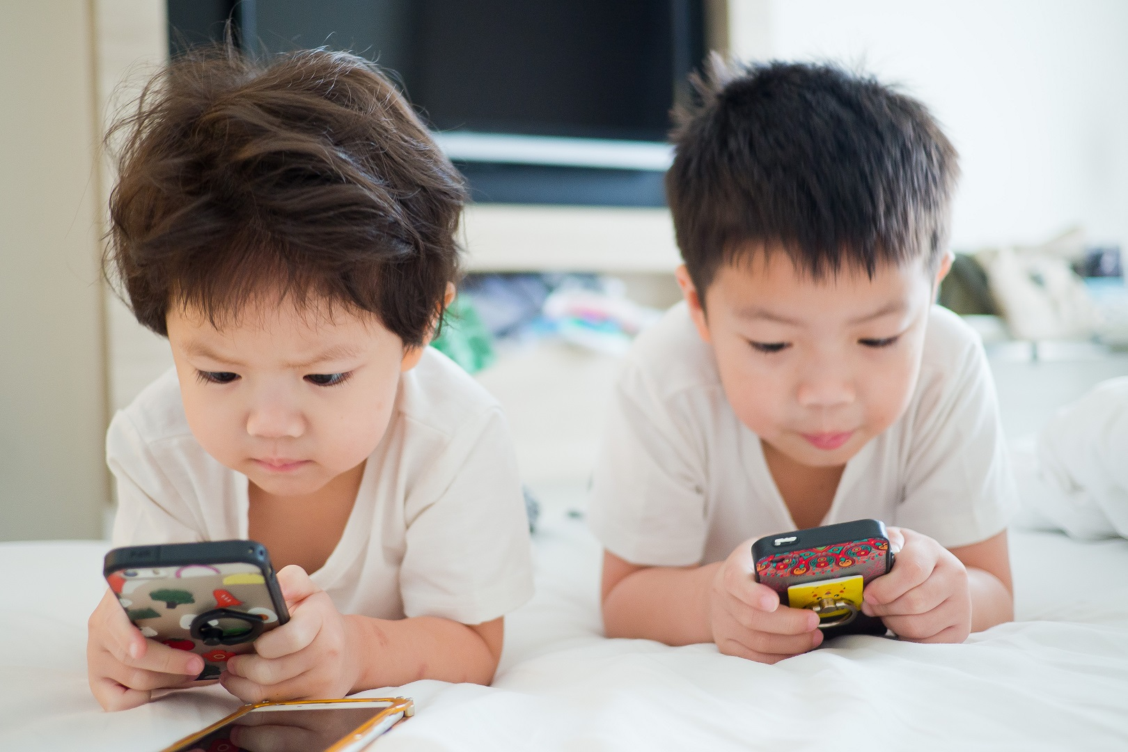 Two Asian Boys Playing On Cell Phones