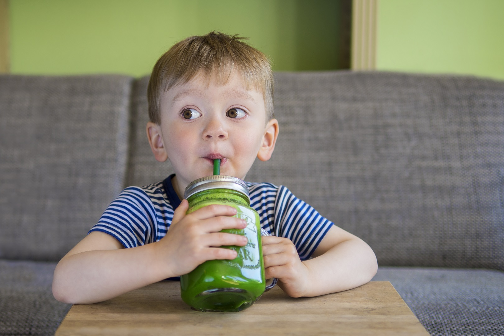 Young Boy Sipping Green Smoothie From Straw In Mason Jar