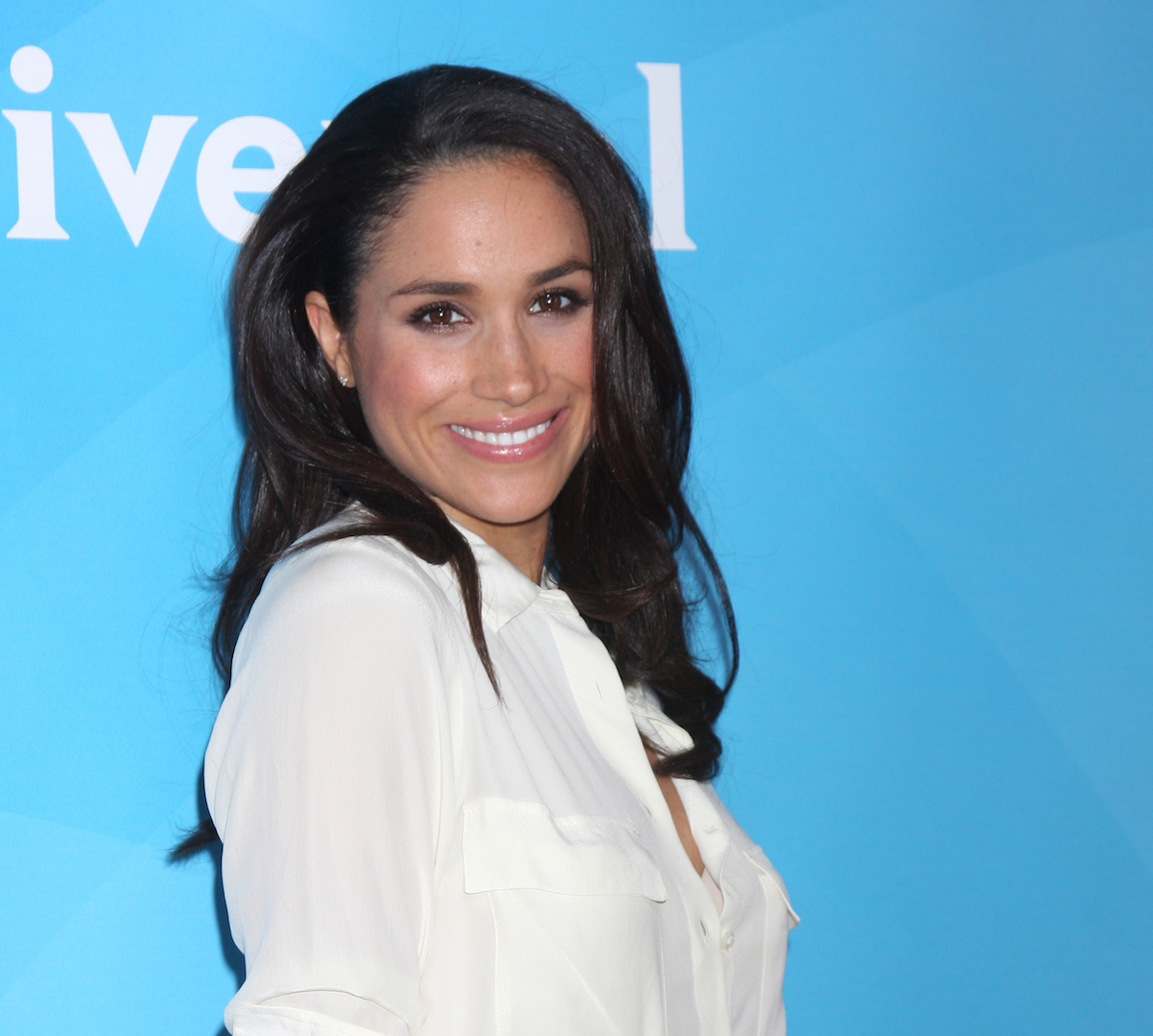 Meghan Markle on Red Carpet White Blouse Blue Background