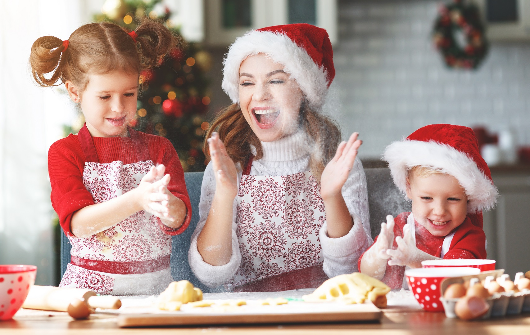 Mother and Children Baking for the Holidays Wearing Santa Hats