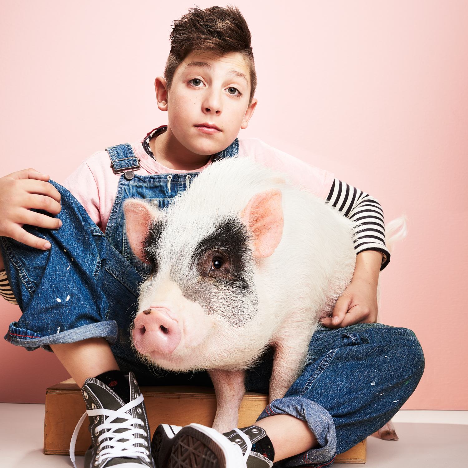boy in denim overalls sitting with potbellied pig