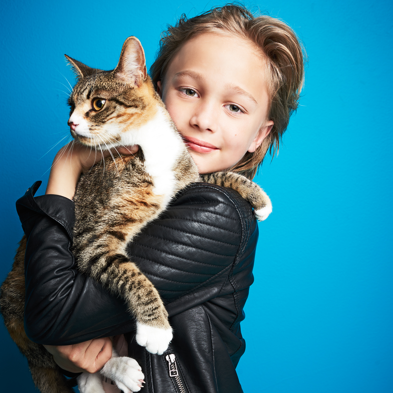 boy wearing black leather jacket holding domestic shorthair kitten