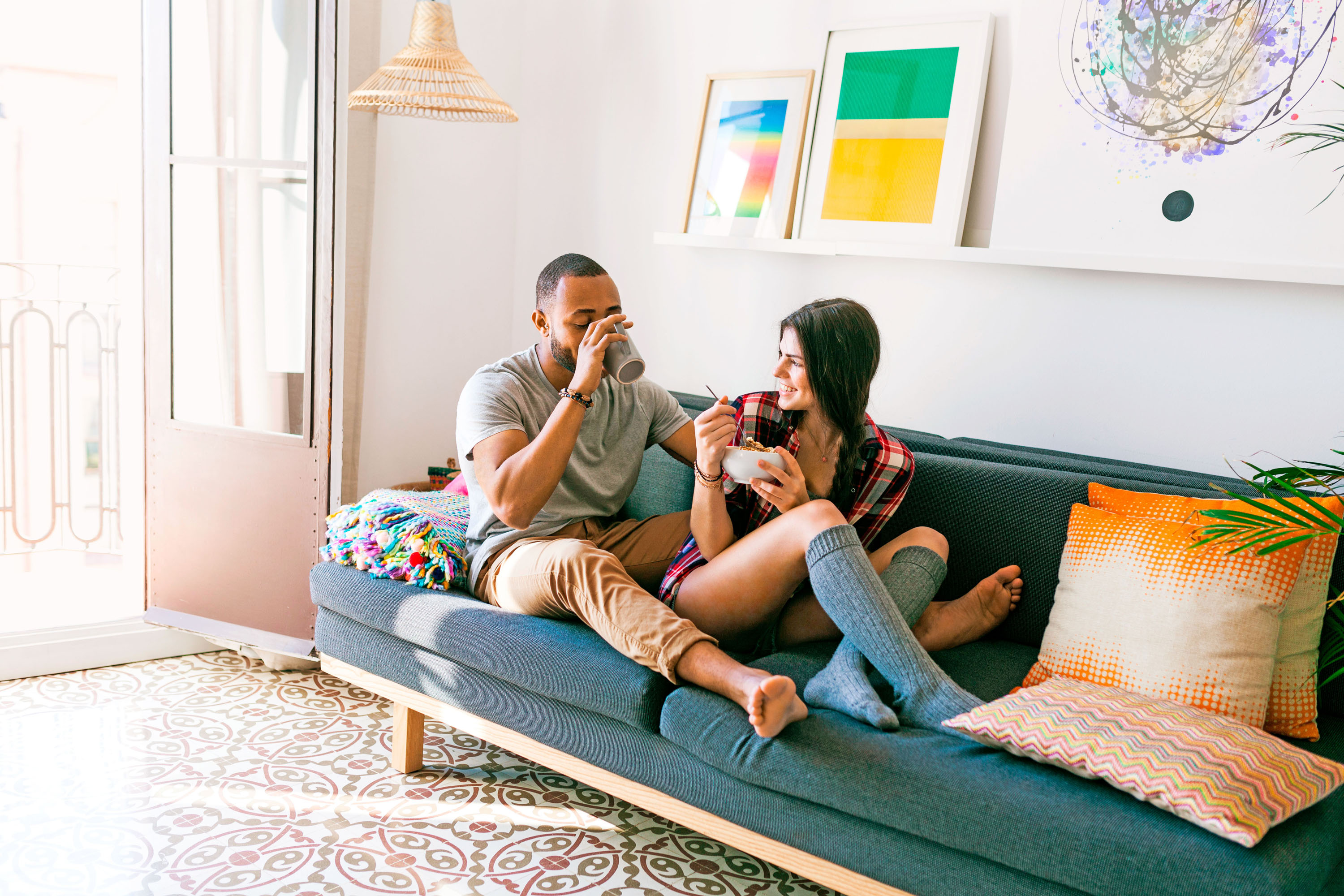 couple sitting on couch eating and drinking together