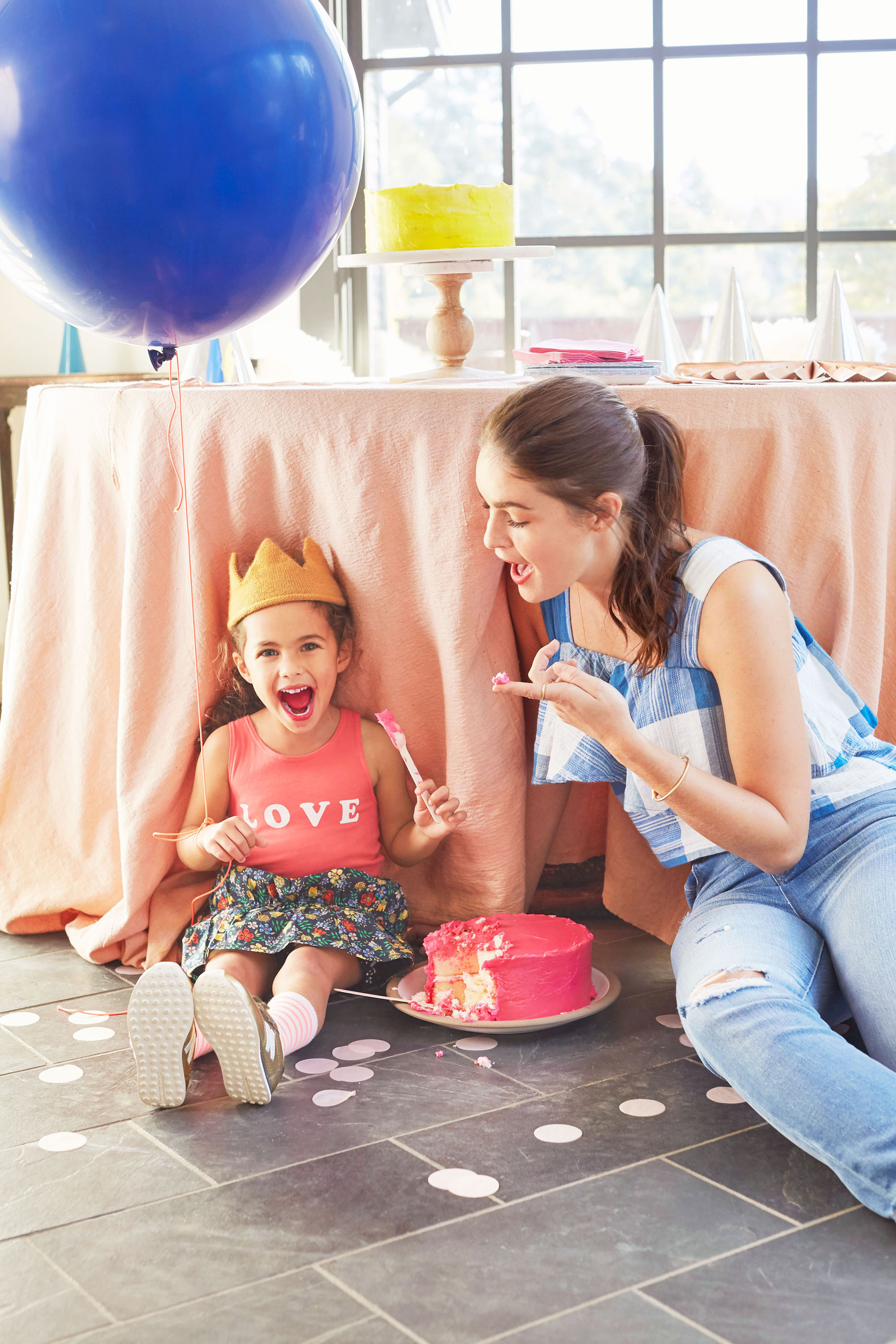 Girl and Mom enjoying Birthday Cake with blue baloon