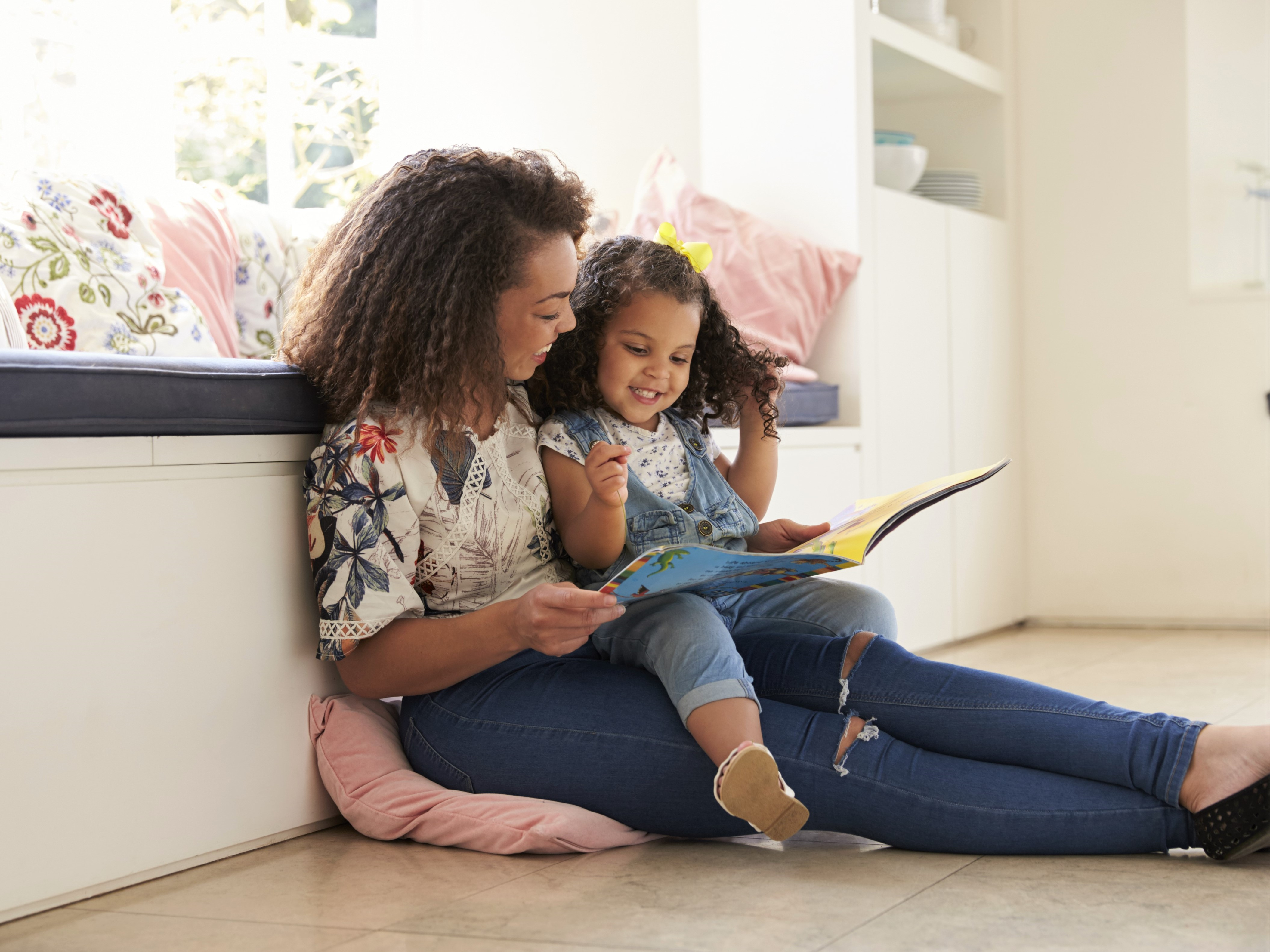 Mother and Daughter Reading Book Sitting on Floor