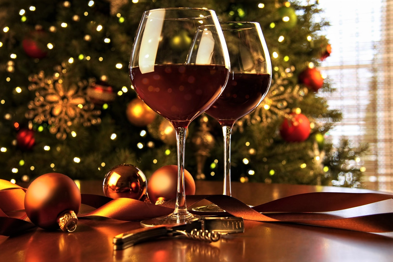 Red Wine Glasses on Table In Front of Christmas Tree