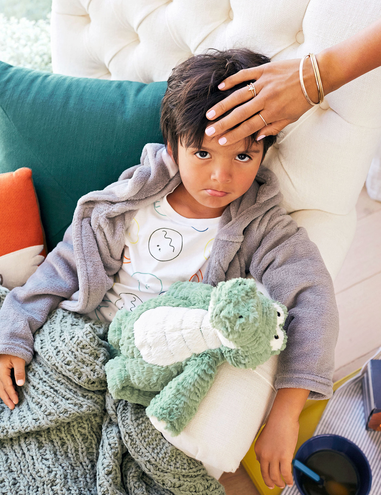 sad young boy on chair with fever
