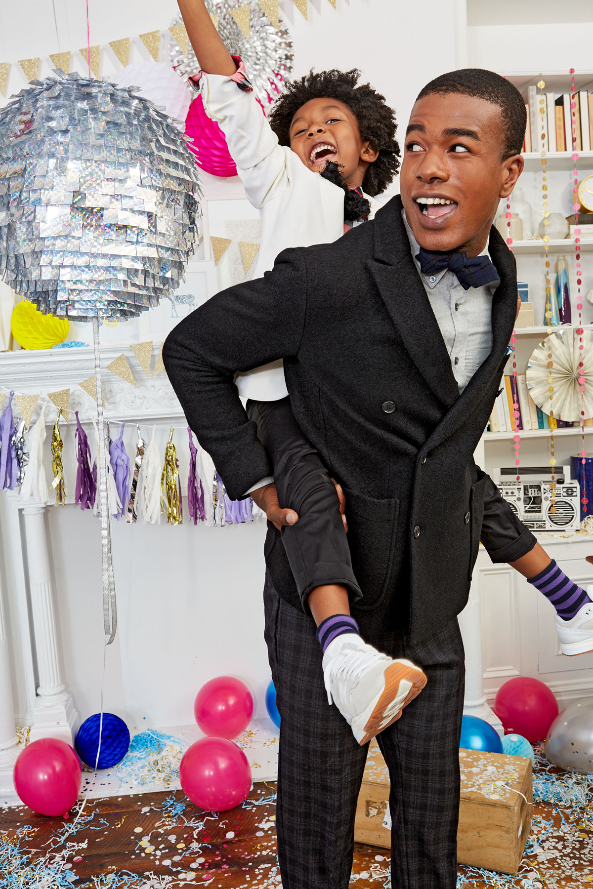 kid riding piggyback on dad with balloons and disco ball decorations