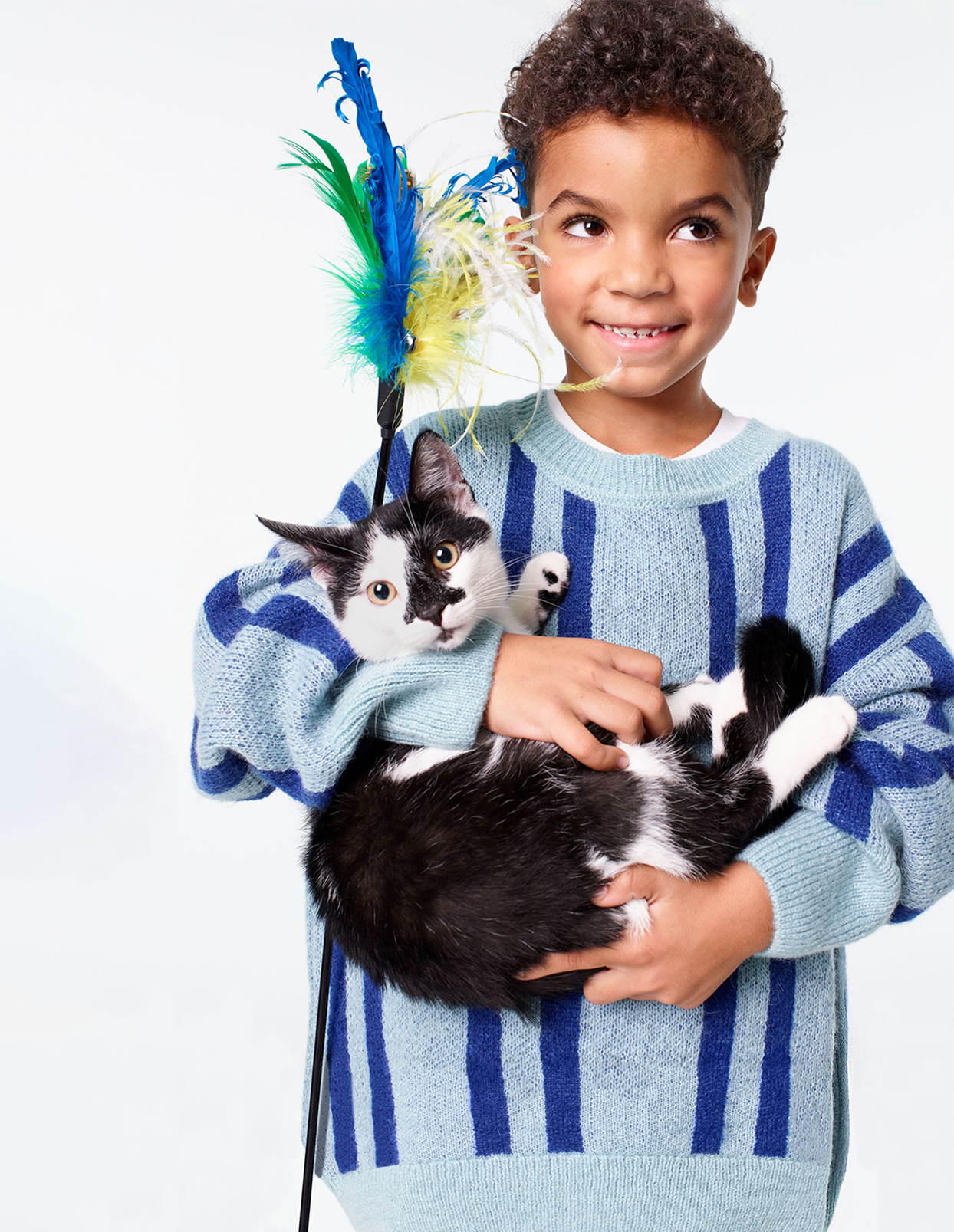 boy in striped sweater holding cat