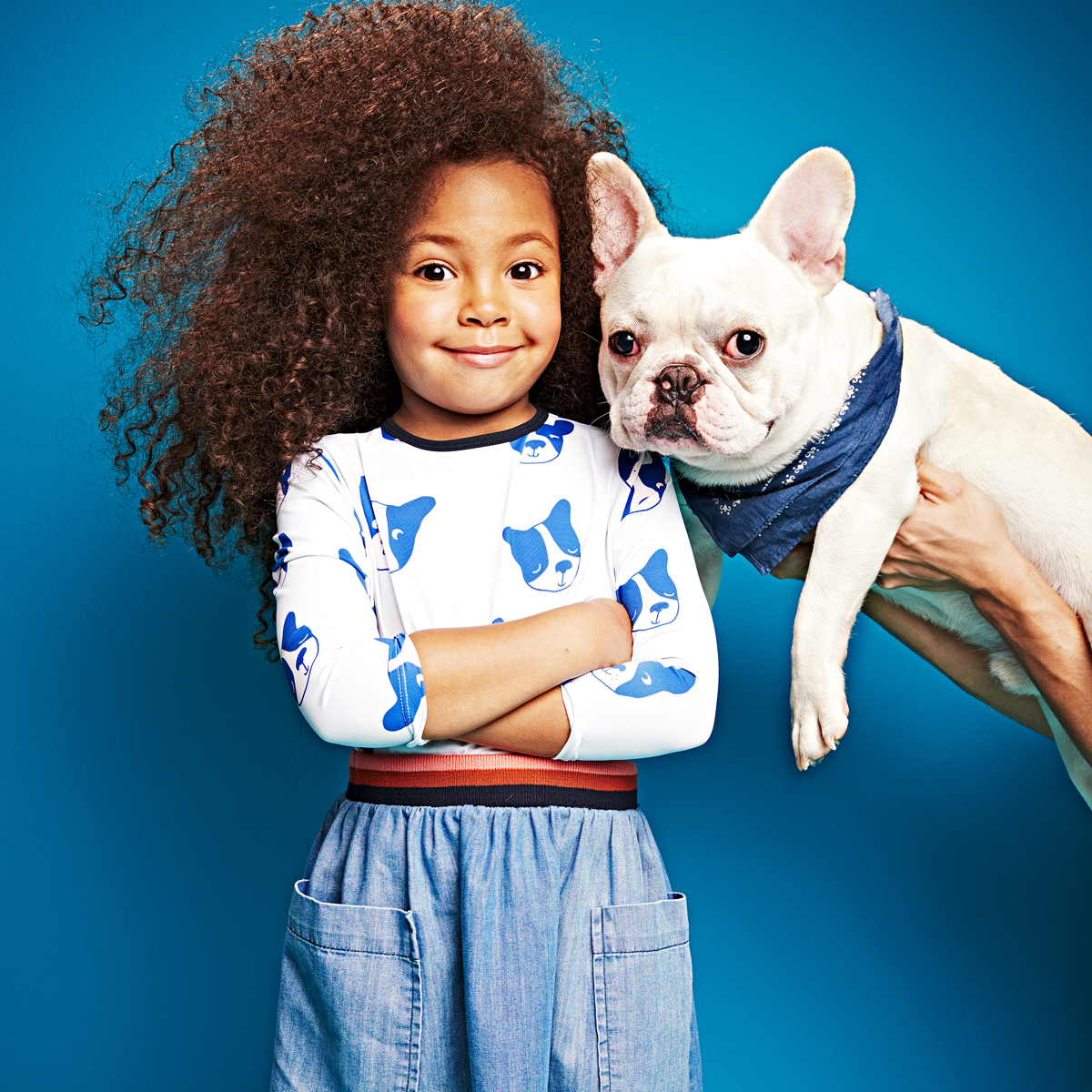 girl with curly hair standing with her arms crossed next to a white french bulldog