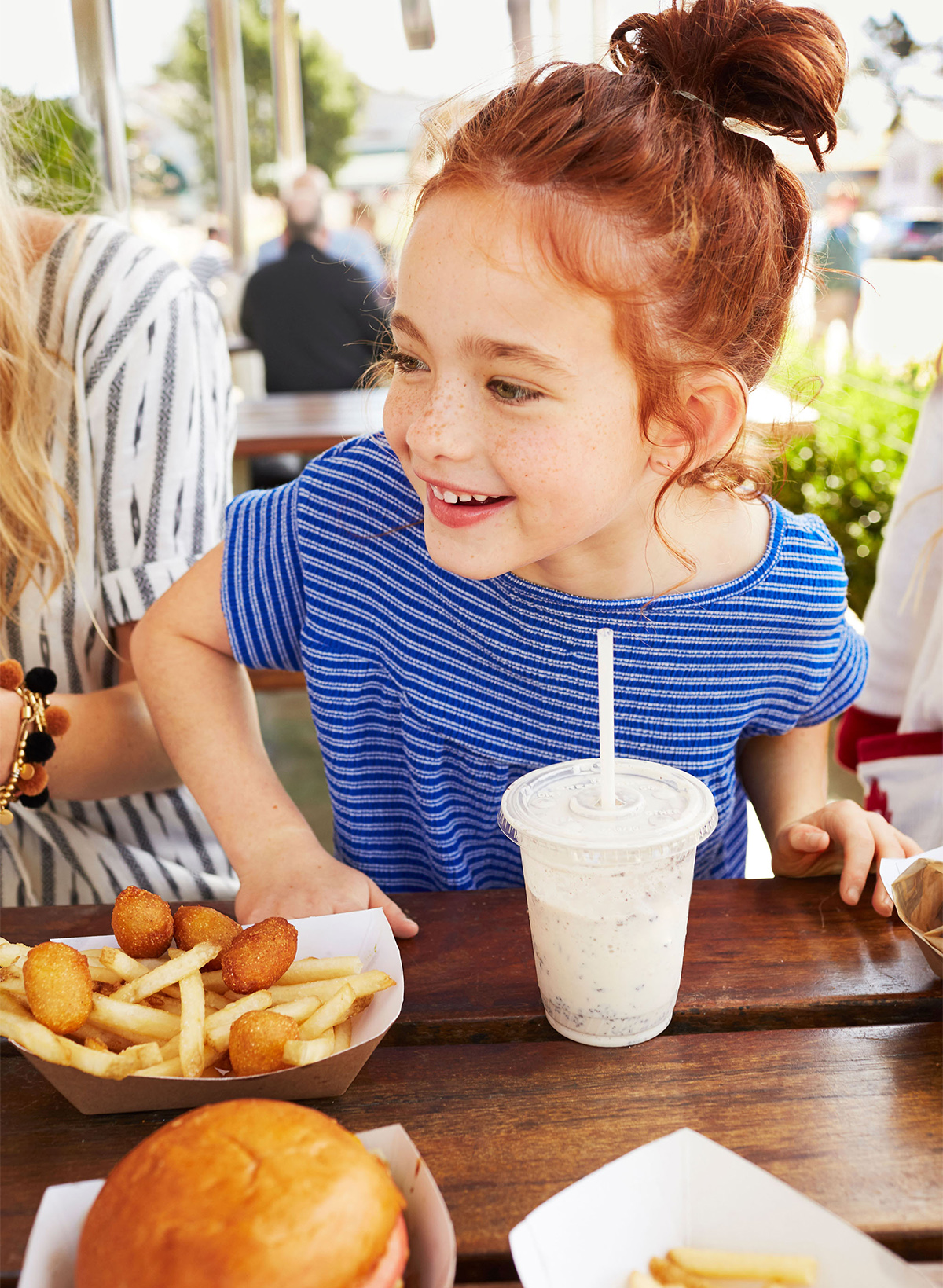 Little red-headed girl at restaurant table smiling