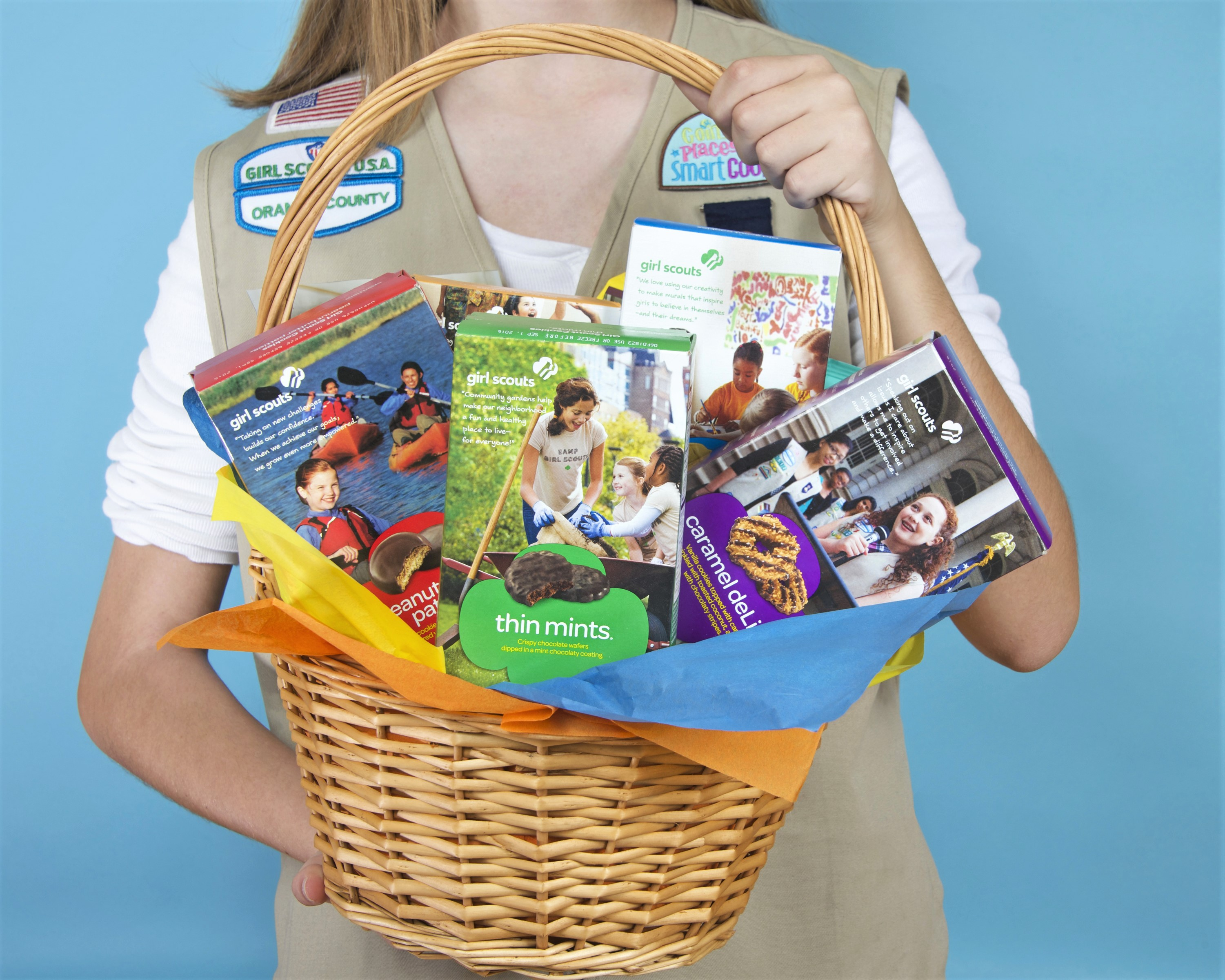 Girl Holding Basket of Girl Scout Cookies Blue Background