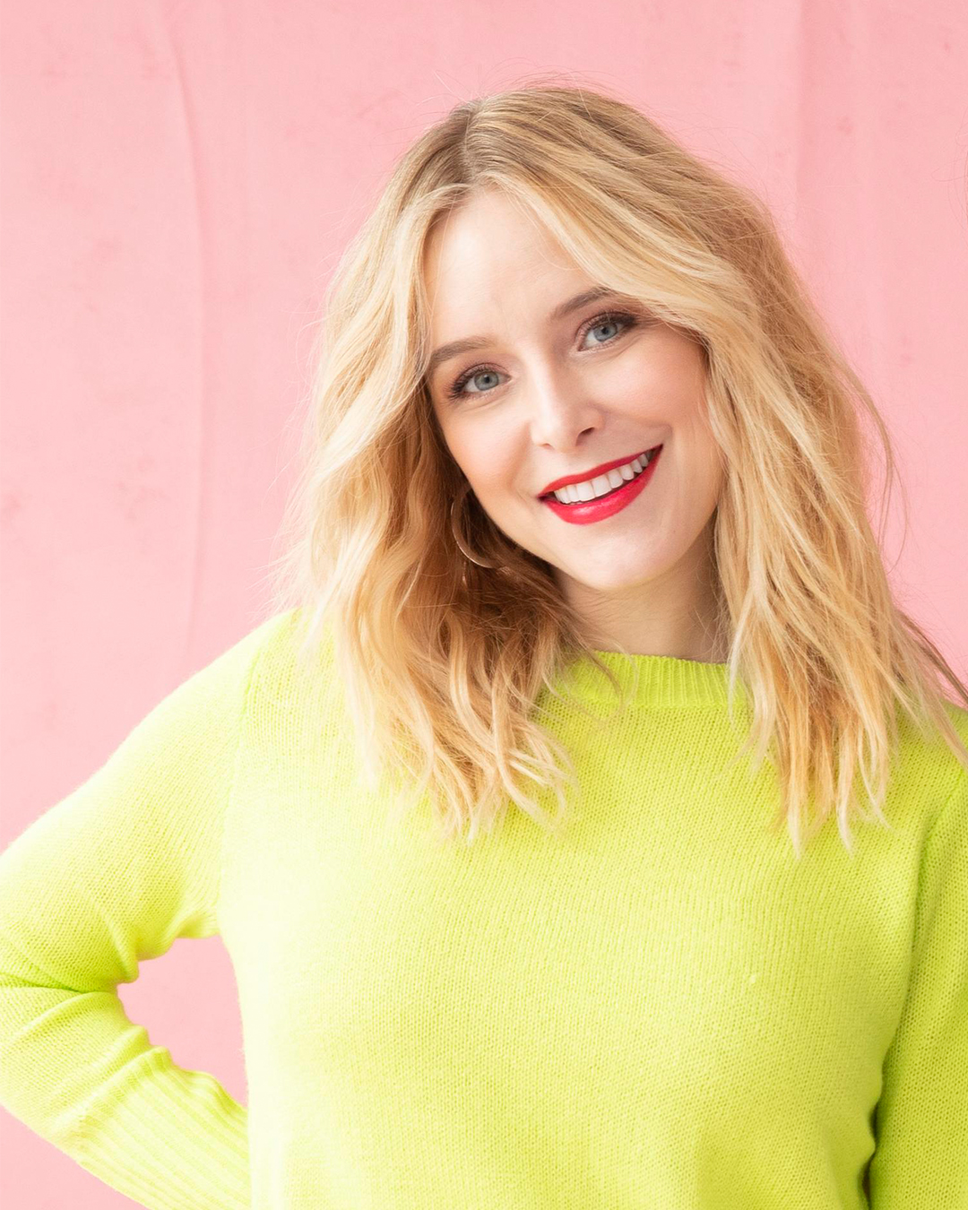 Jenny Mollen headshot wearing neon yellow sweater against pink backdrop
