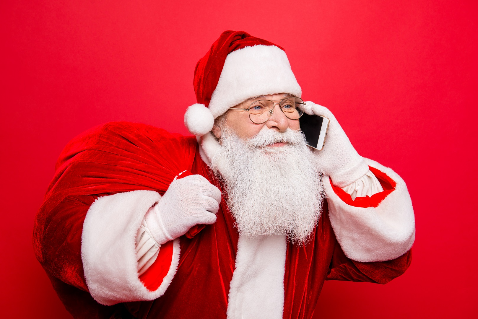 Santa Claus Talking on Phone Holding Bag of Presents Red
