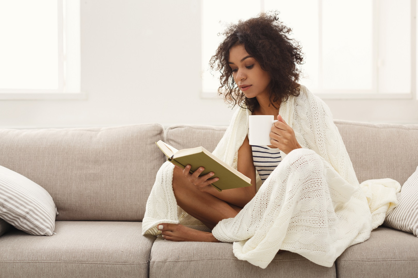 African American Woman Reading Book on Sofa White Blanket and Mug