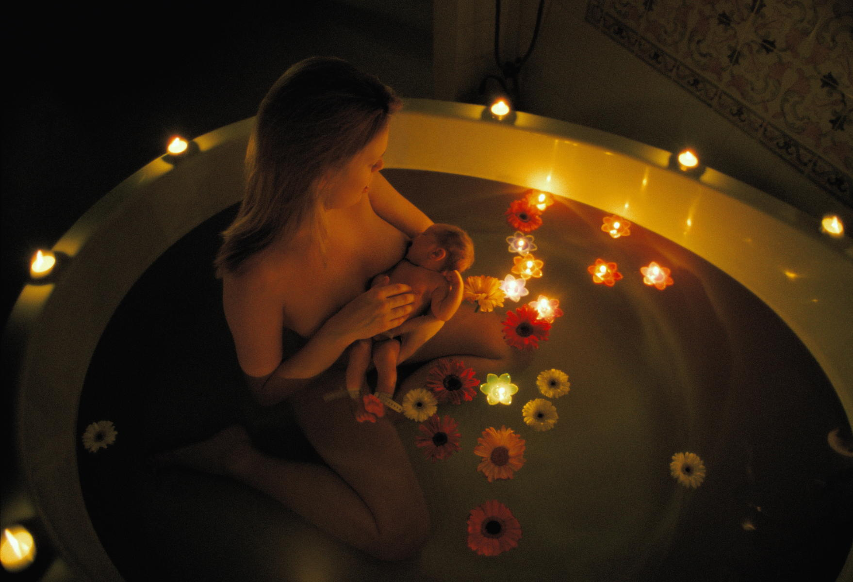 Mother breastfeeding newborn baby girl in candlelit bath with flowers