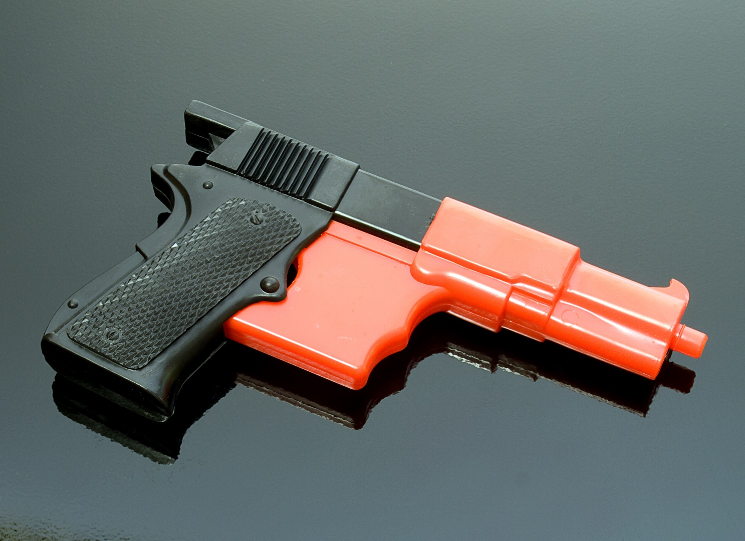 Black and Orange Toy Gun on Shiny Black Surface