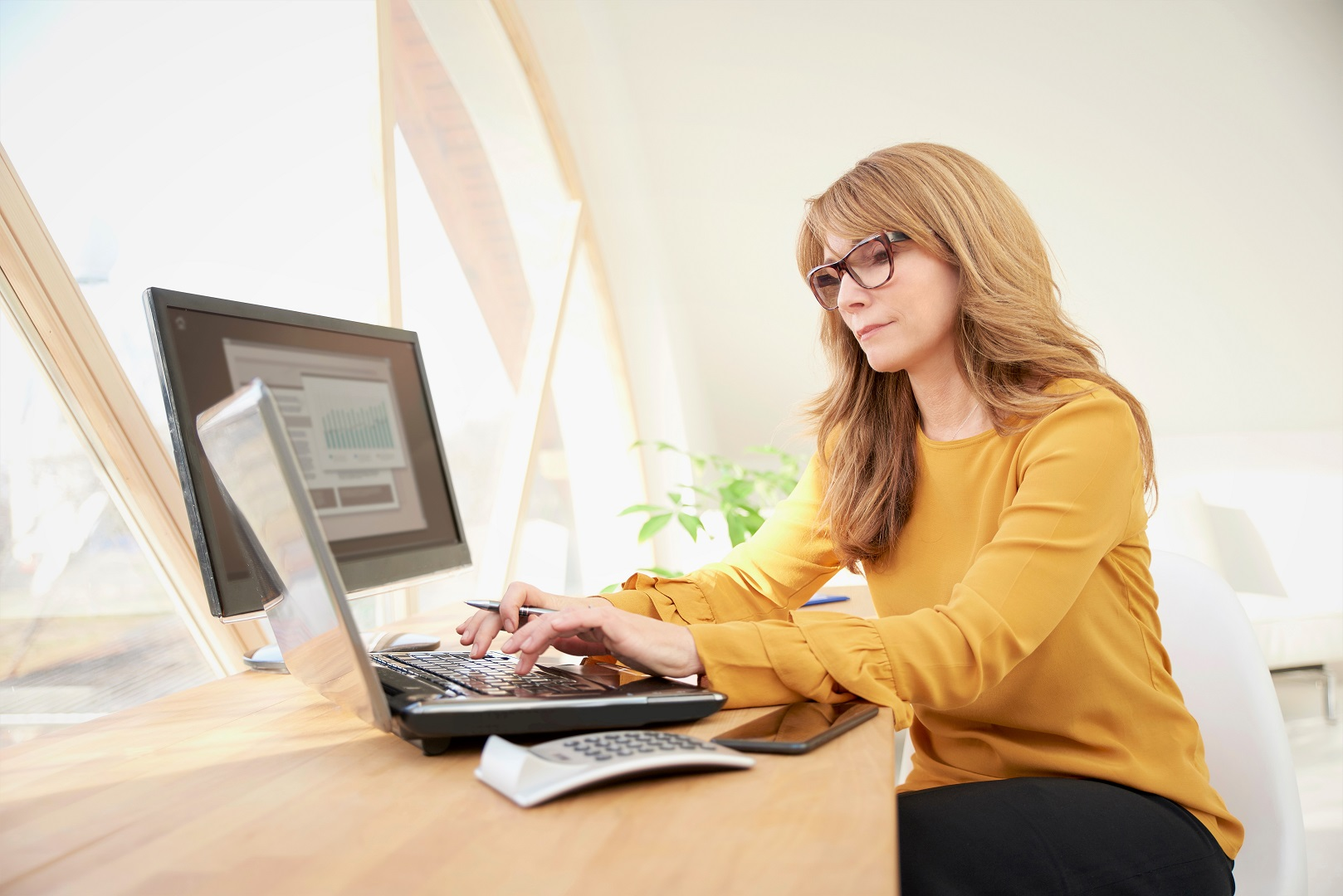 Yellow Shirt Woman Working on Laptop and Desktop