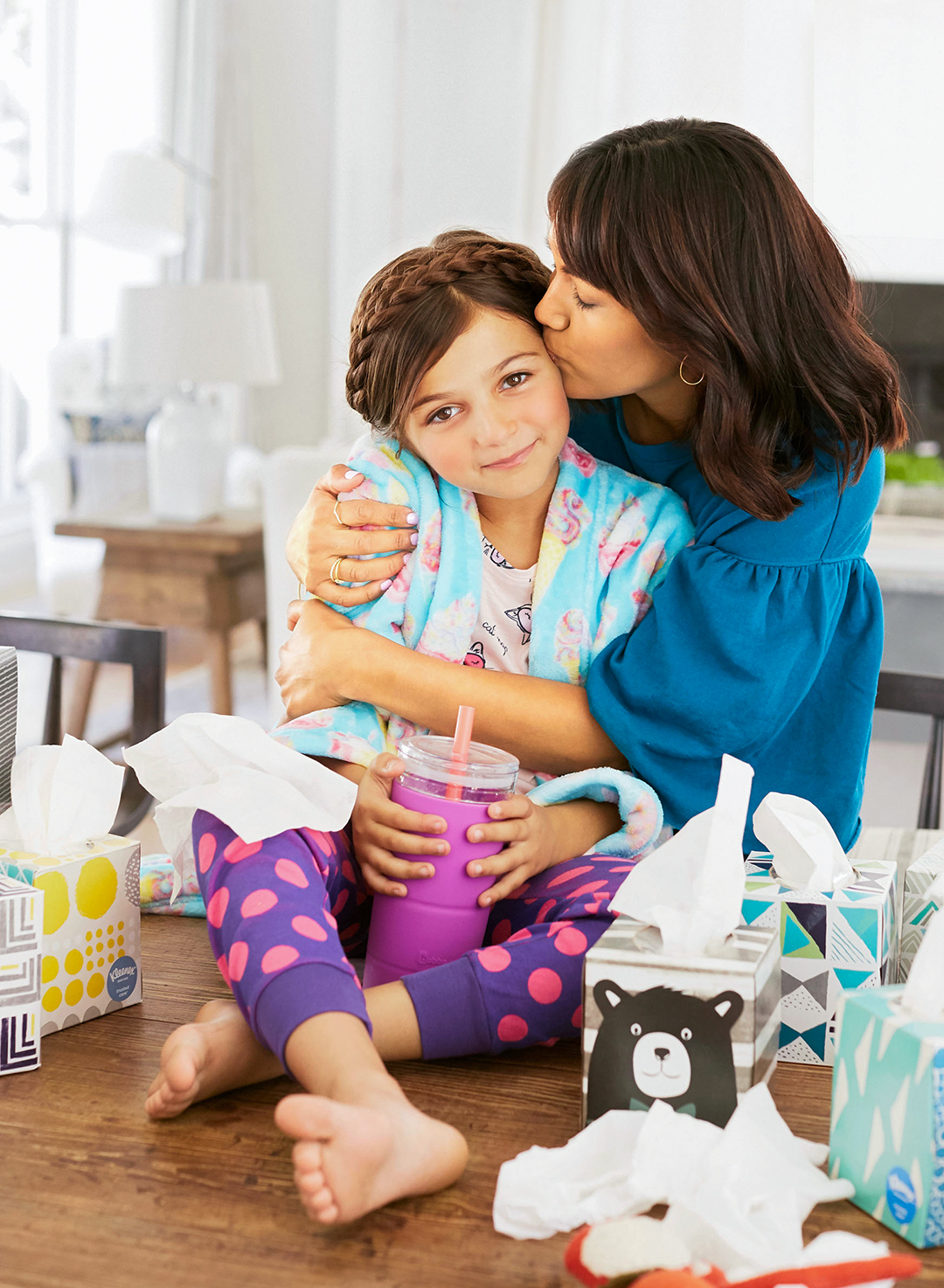 mom hugging daughter kitchen table with kleenex