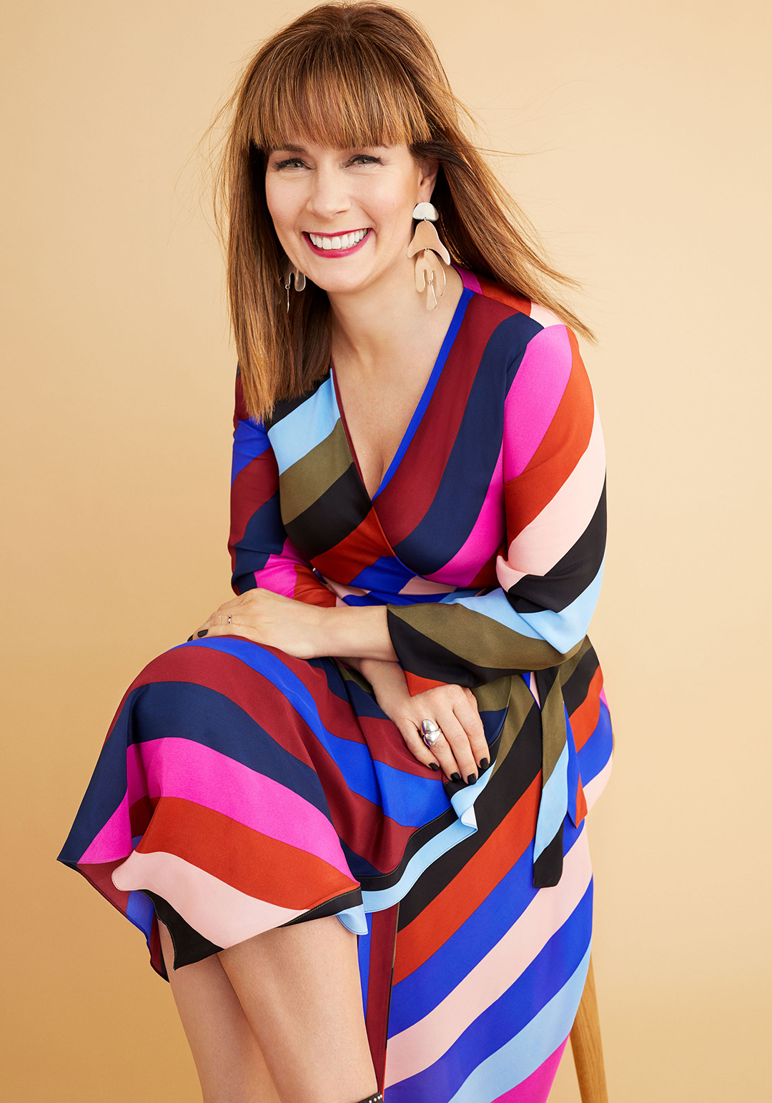 woman smiling wearing colorful dress