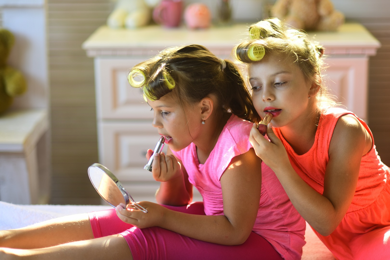 Two Young Girls Wearing Hair Rollers Putting On Lipstick Looking in Mirror