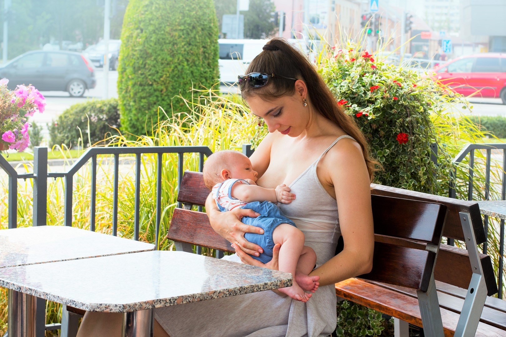 Young Mother Public Breastfeeding on Bench Outside