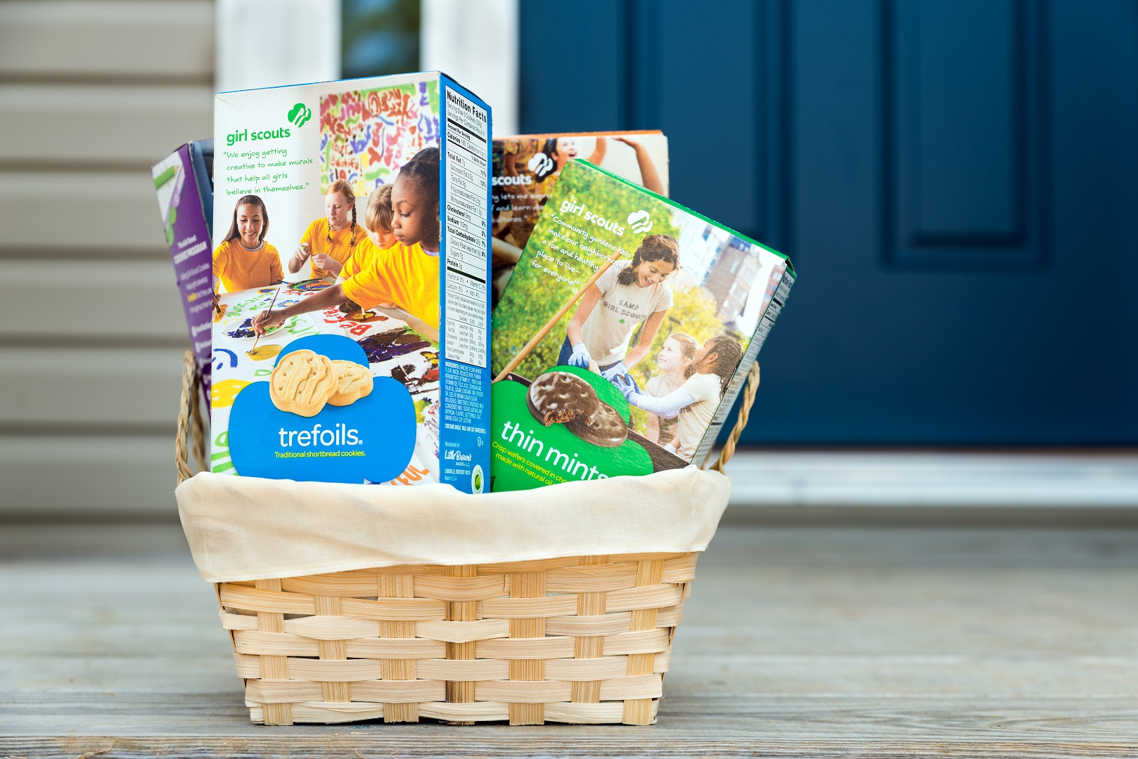 Boxes of Girl Scout Cookies in Basket on Doorstep