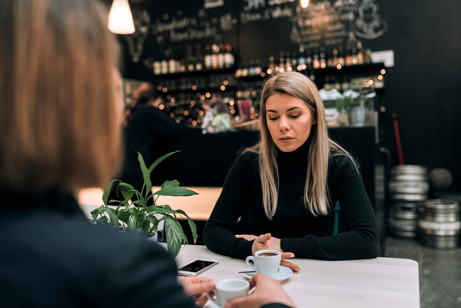 Sad Woman At Cafe With Friend Coffee on Table