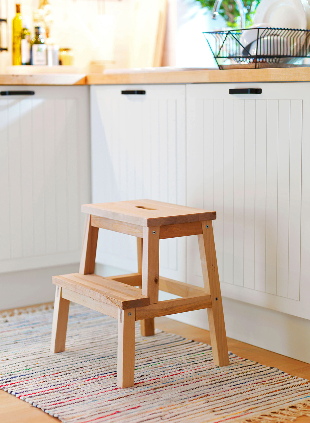 wooden bekvam step stool in kitchen on braided rug