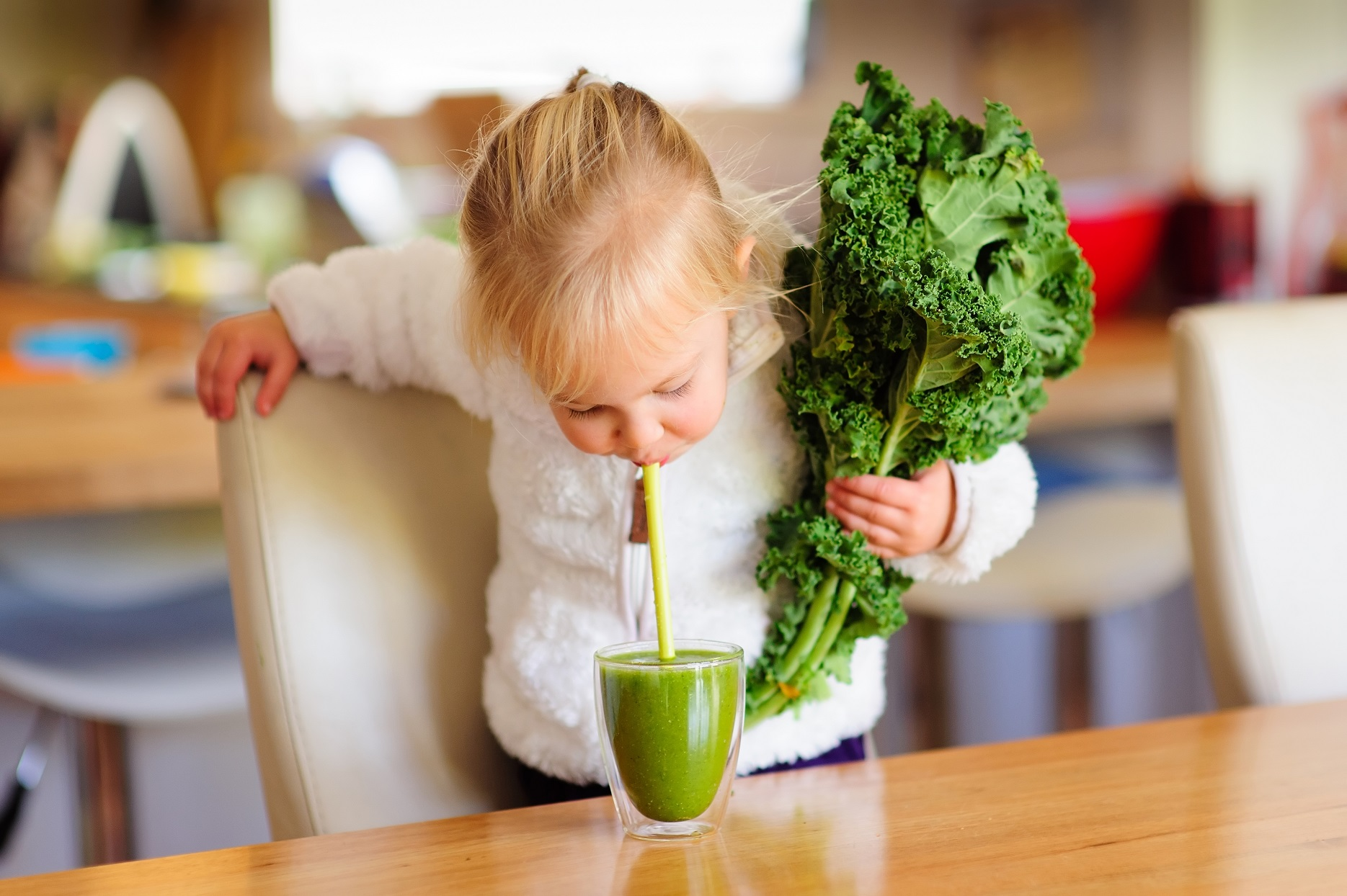 Little Girl Holding Kale Drinking Green Smoothie With Straw