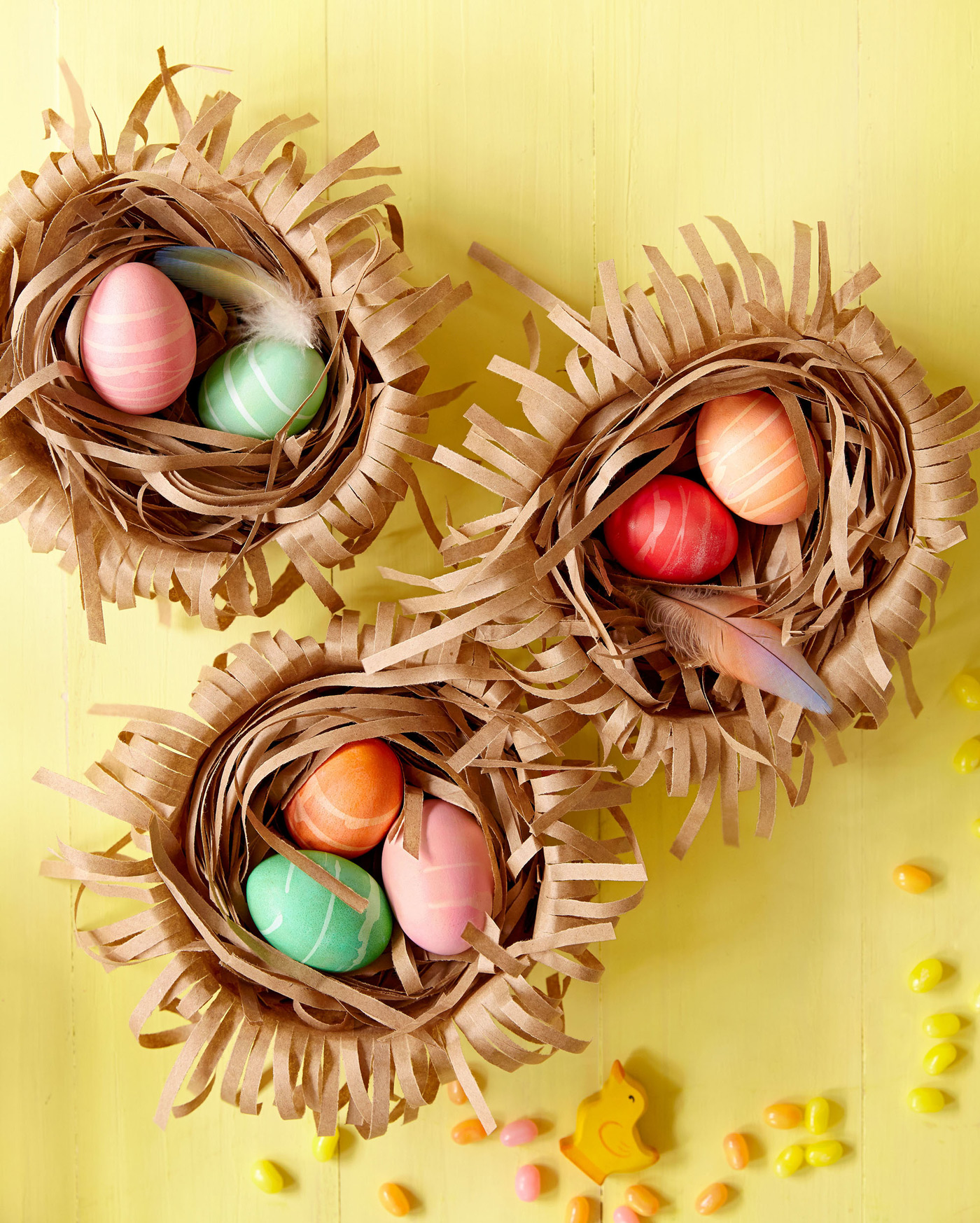 three brown paper nests with colored eggs