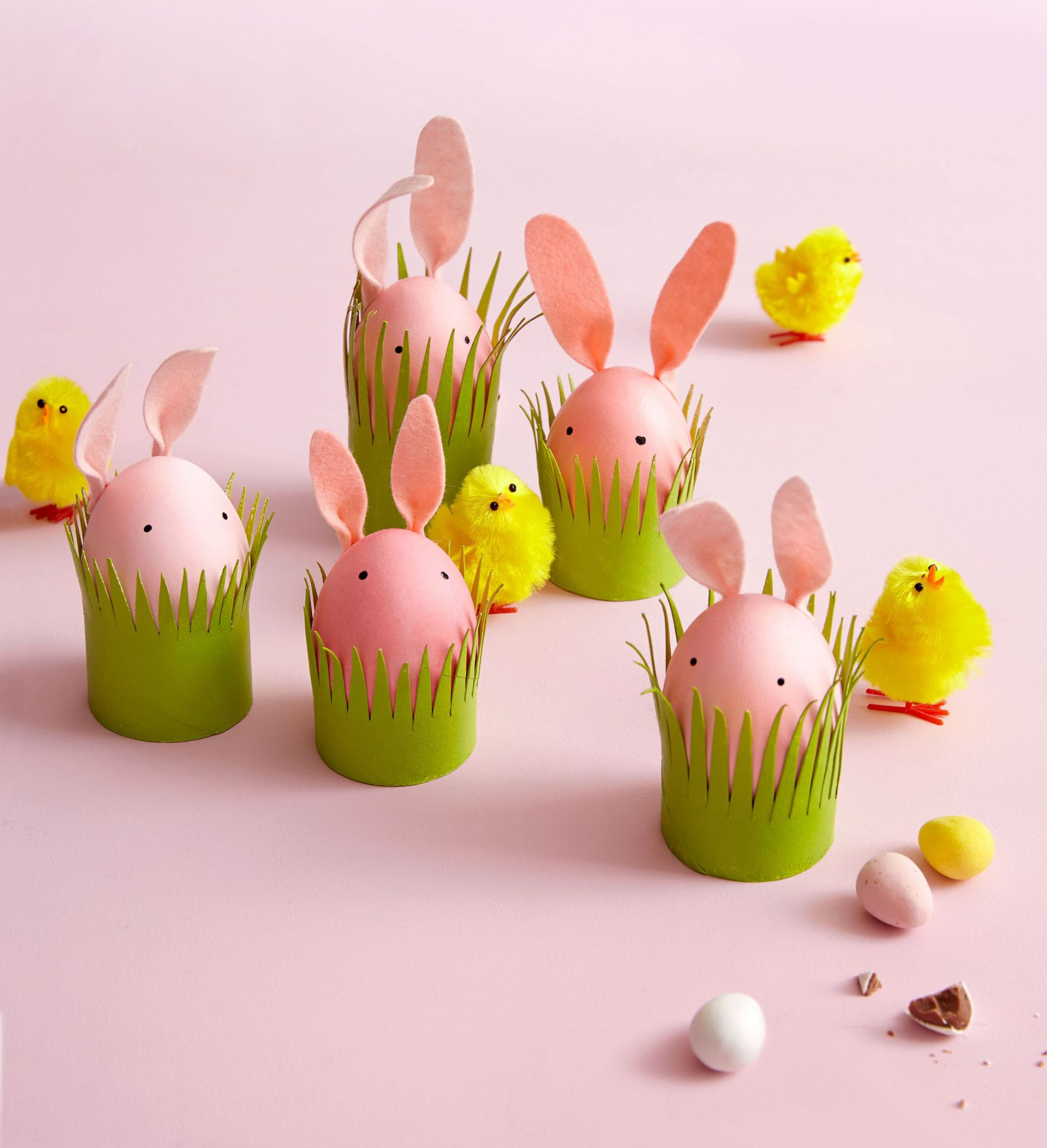 five pink funny bunny's in green grass containers