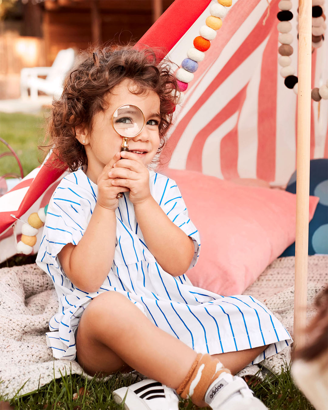 child wearing blue striped dress sitting beneath tent holding magnifying glass