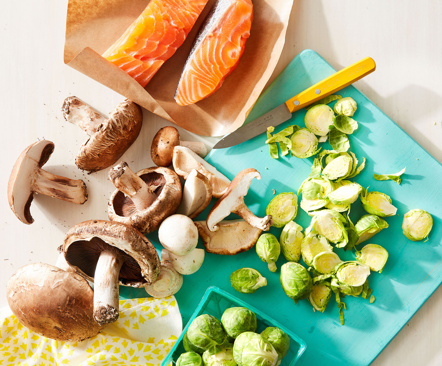 mushrooms brussels sprouts fish on teal cutting board