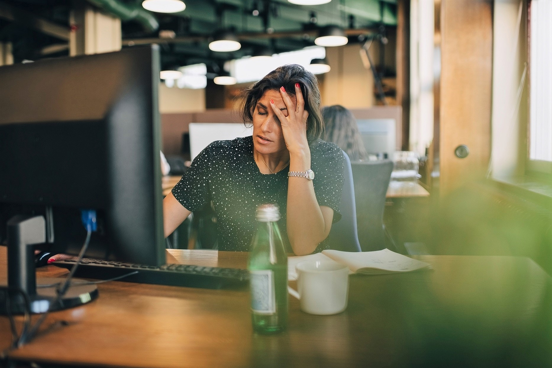 Woman Stressed Sitting In Desk At Work Hand on Face